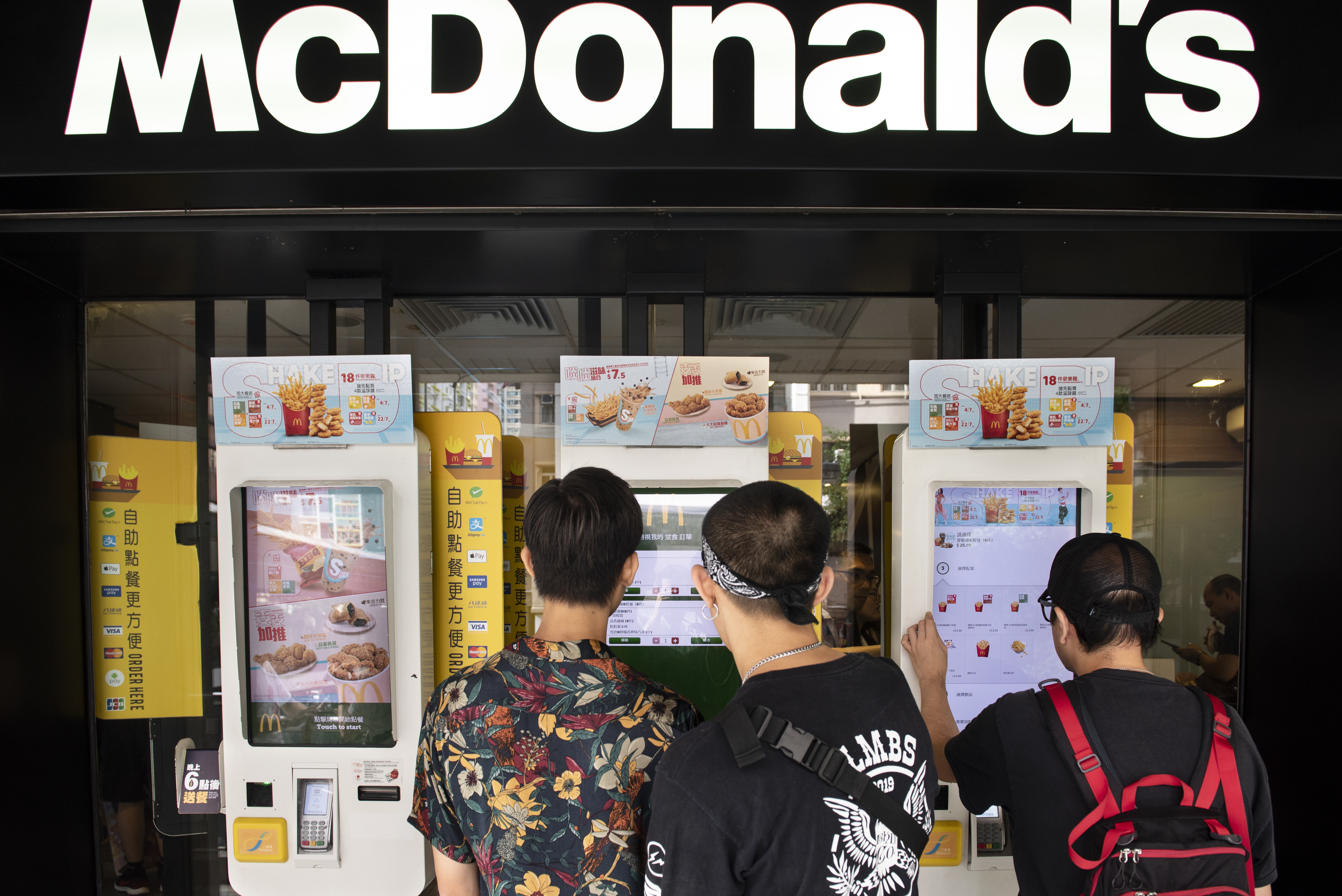 Customers order food in an automated self-ordering kiosk at...