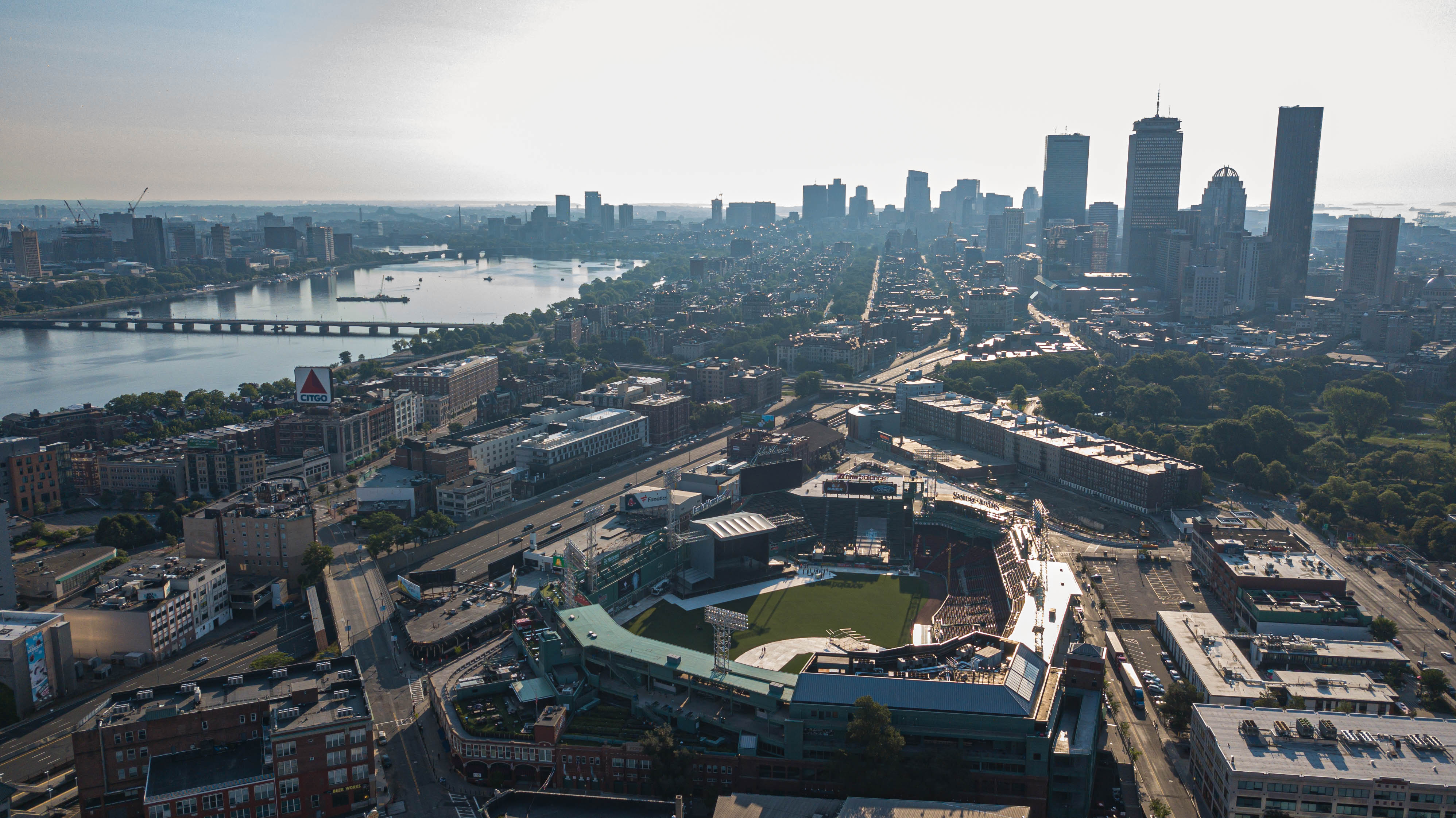 An expansive aerial shot of the Boston area, with a ballpark in the foreground and a cluster of skyscrapers farther away.