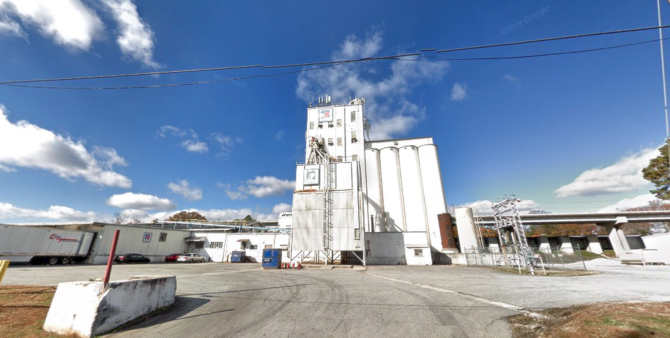 Large white silos flanked by low white buildings and large parking lot.