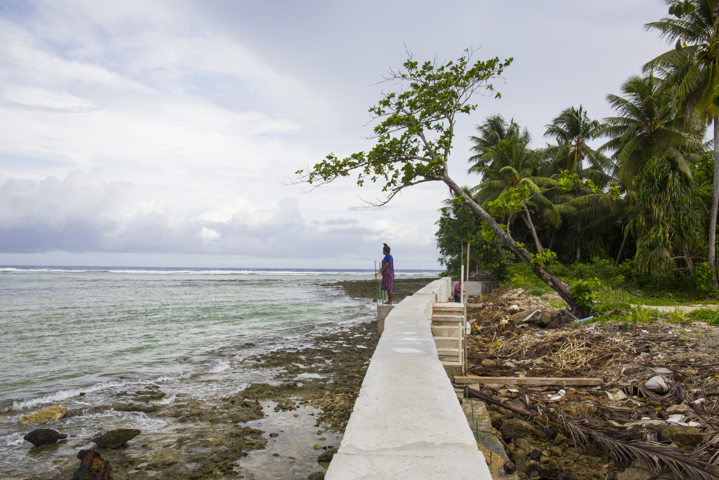 A woman stands on a seawall on Majuro Atoll.