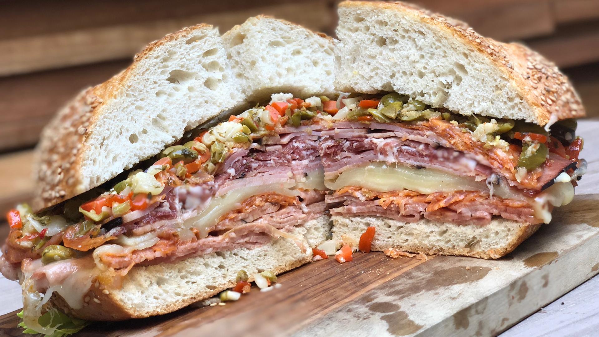 A muffuletta sandwich cut in half on a cutting board