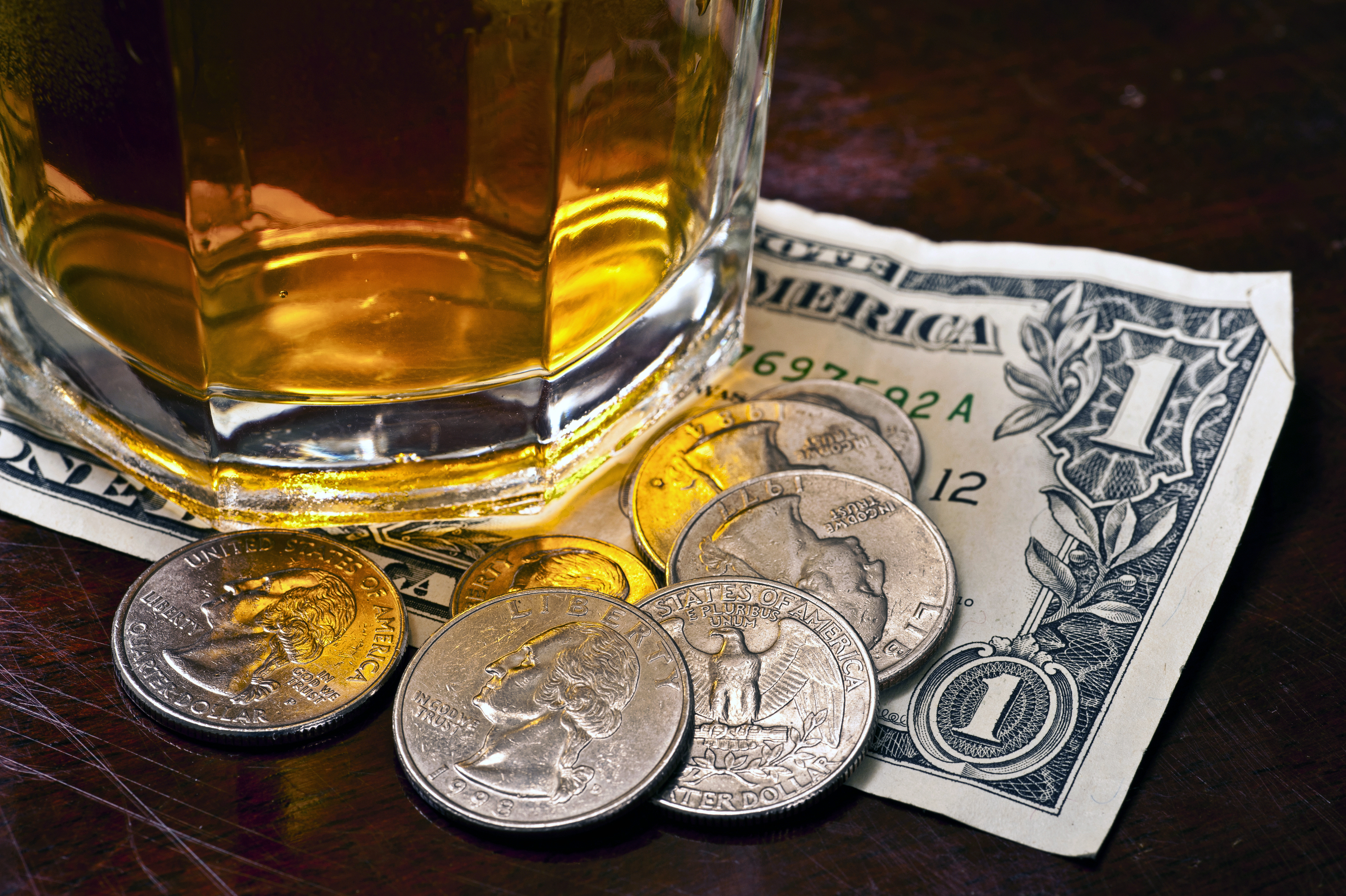 A glass of whiskey sits on top of a dollar bill and some quarters.