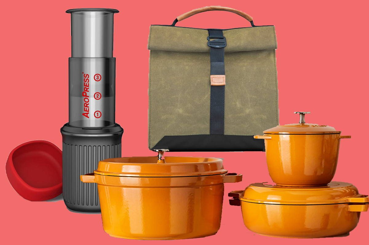 An Aeropress coffee machine, a army-green canvas bag with top-handle, and a set of pumpkin-colored Staub pots, all on a pink background