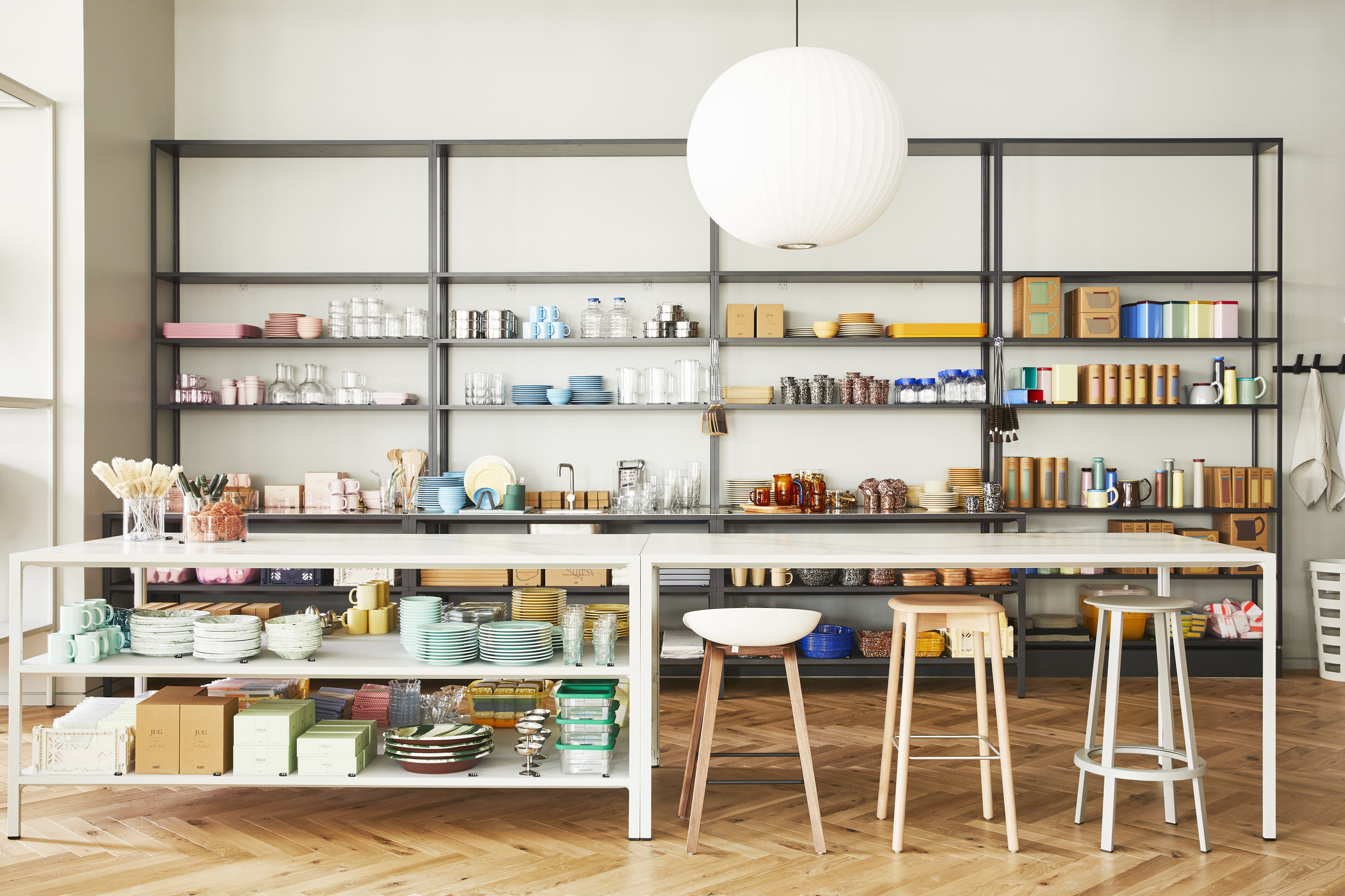 A gallery with shelves with stacks of modern yet colorful plates, cups, utensils, and serving dishes.