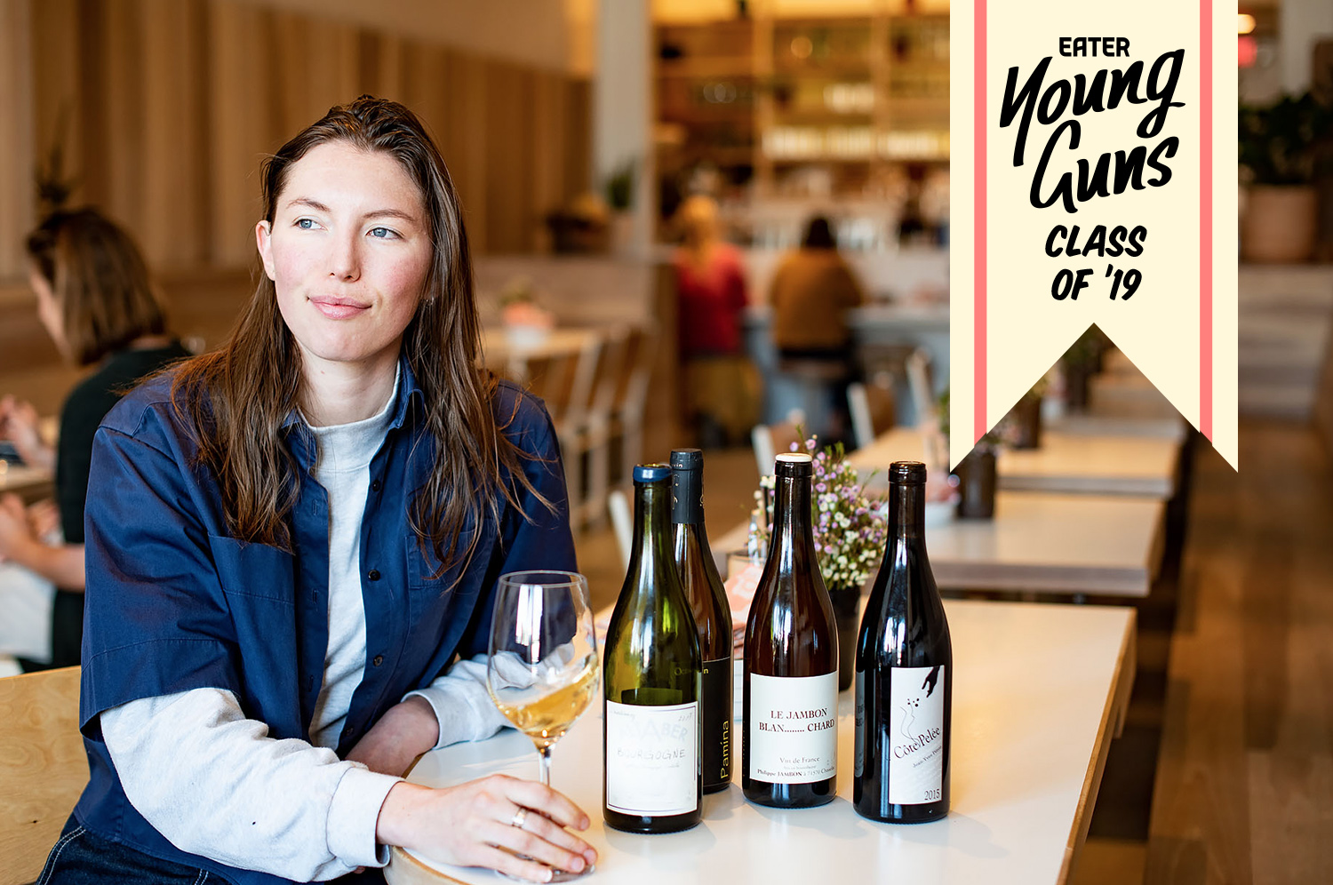 Kae Whalen sits at a table with with wine bottles in the Kismet dining room.