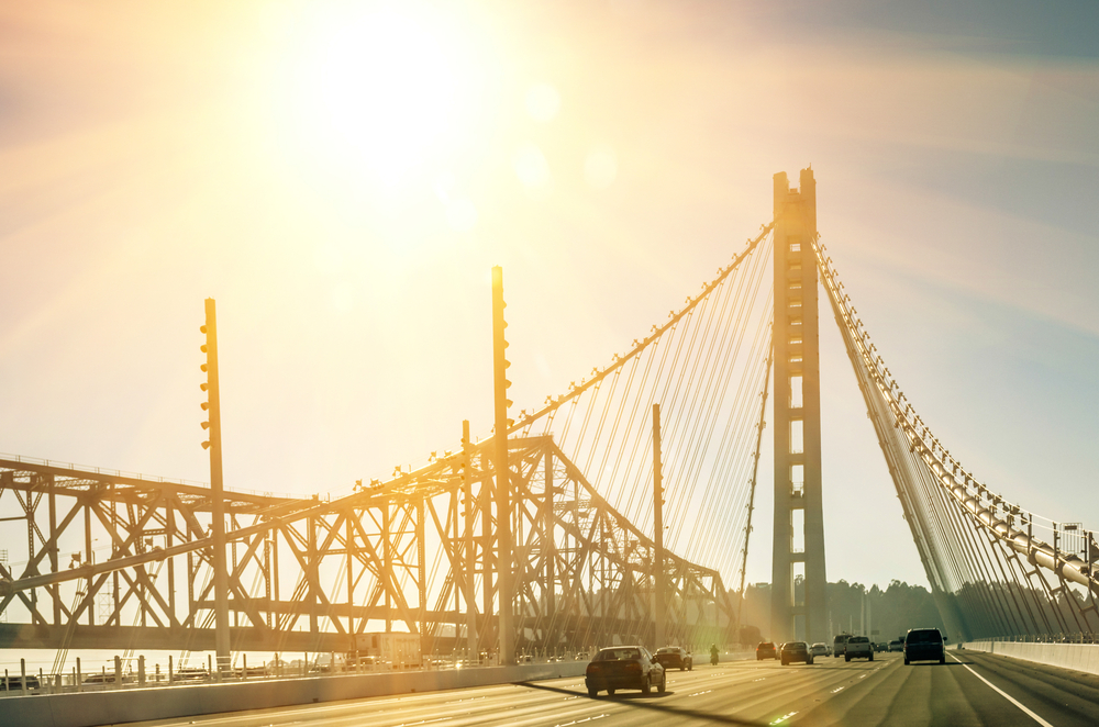 The glare of the sun over a suspension bridge with a single tower.