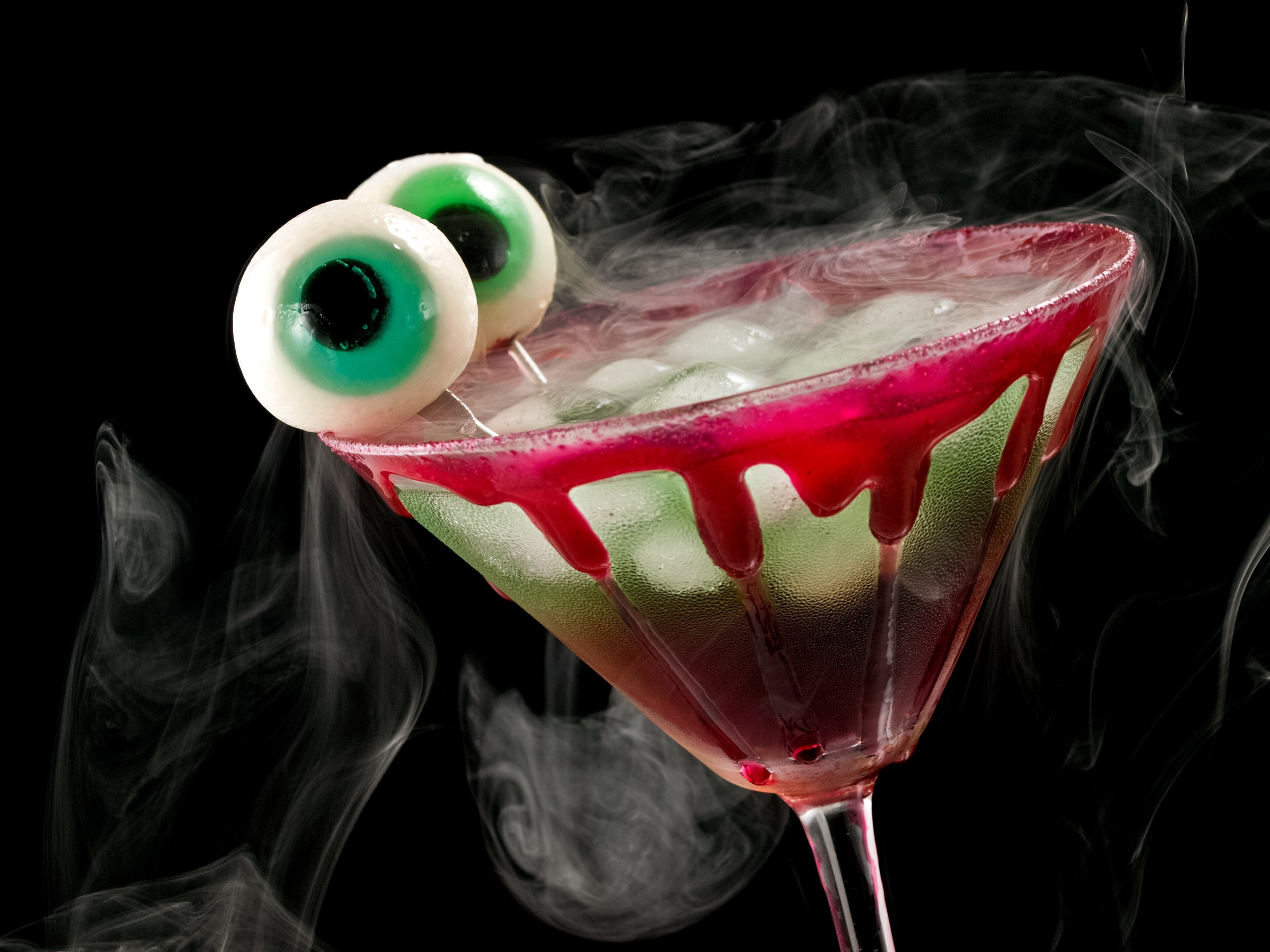a martini glass with fake blood on the side and two fake eyeballs sticking out of it