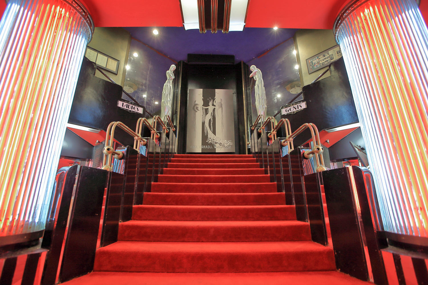 Red-carpeted stairs in the Art Deco style with glowing, lit-up columns.
