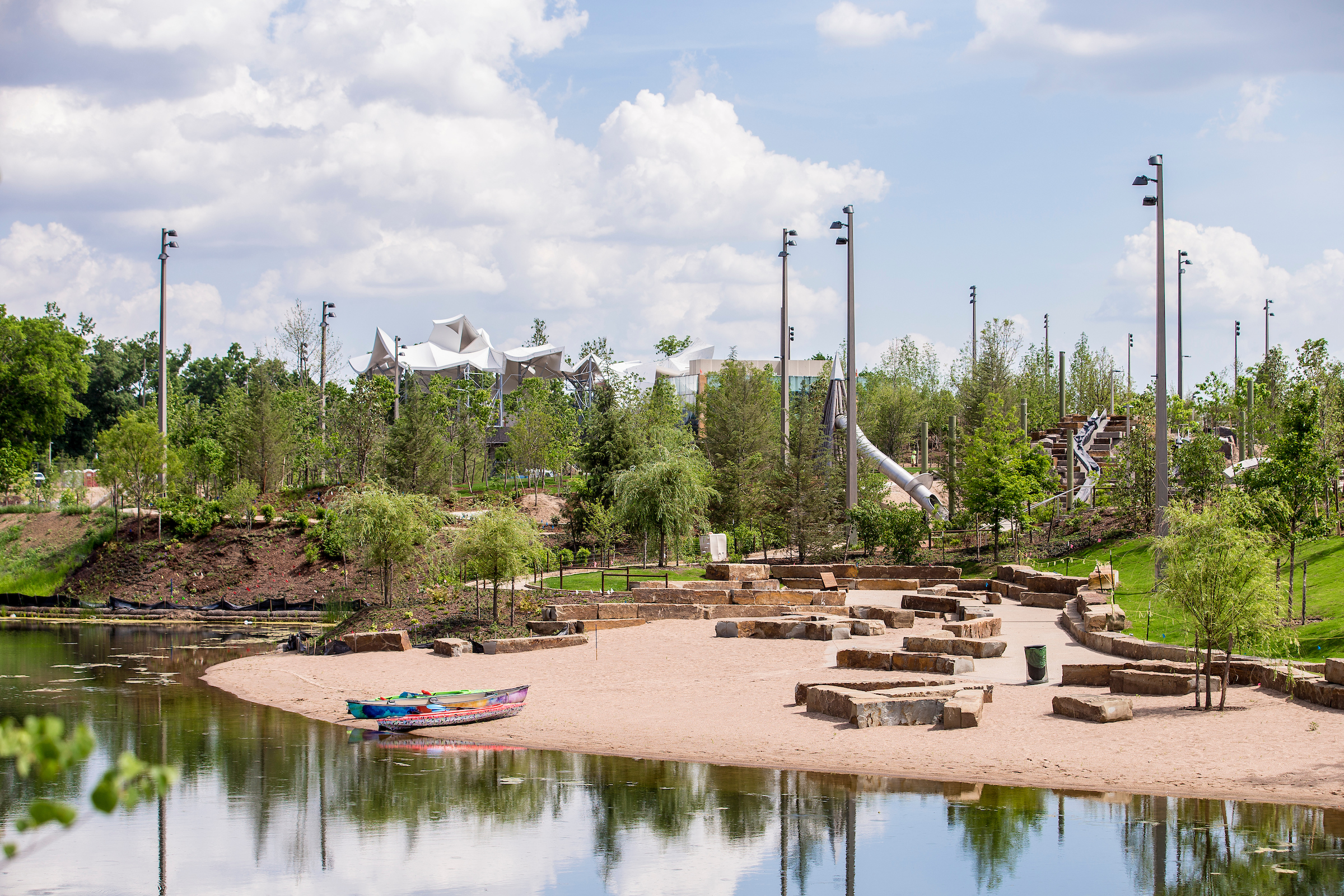 A park with benched seating on a manmade shore. There are silver slides in the background.