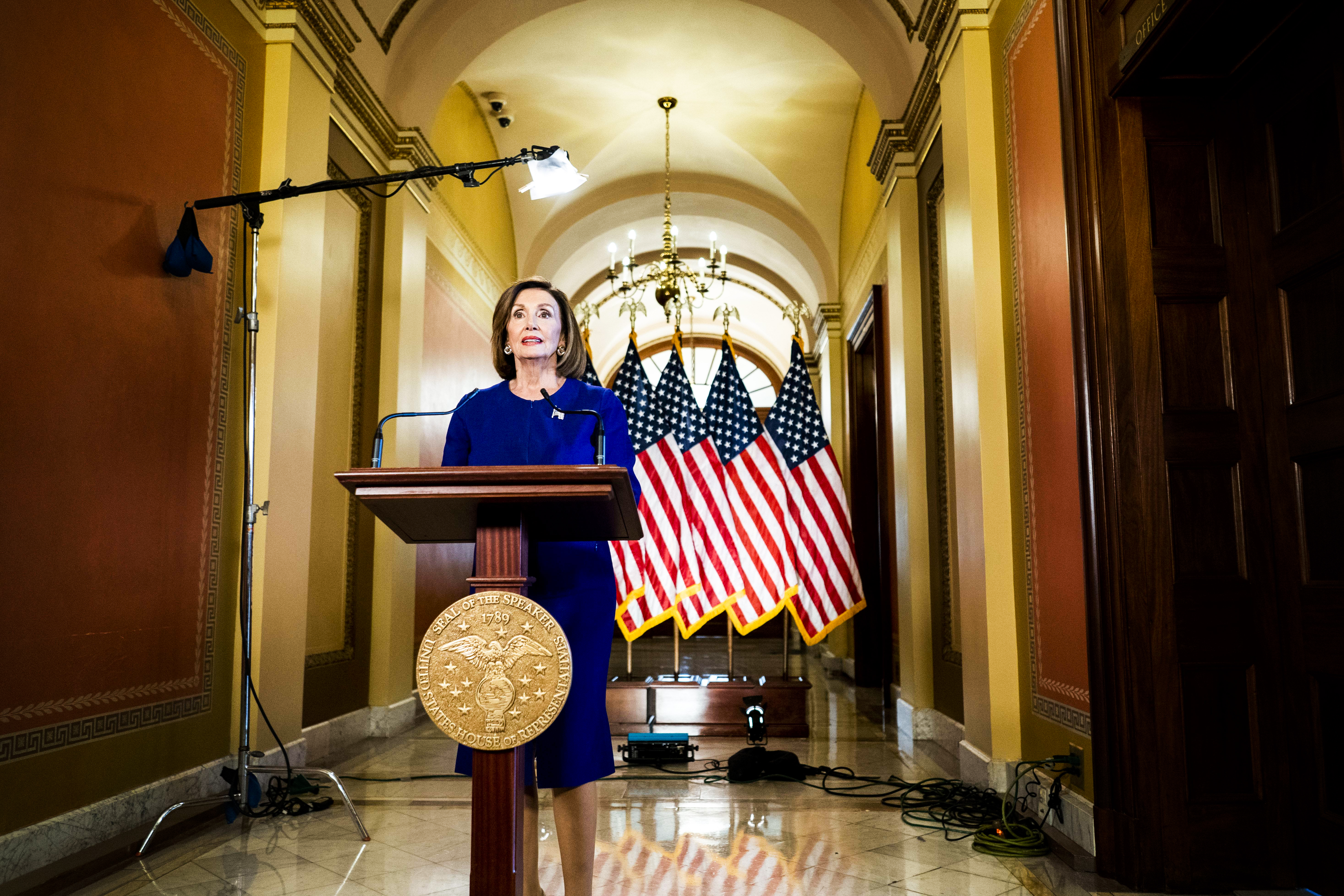 Speaker of the House Representative Nancy Pelosi speaks to the press at a podium set up in a hallway outside her office.
