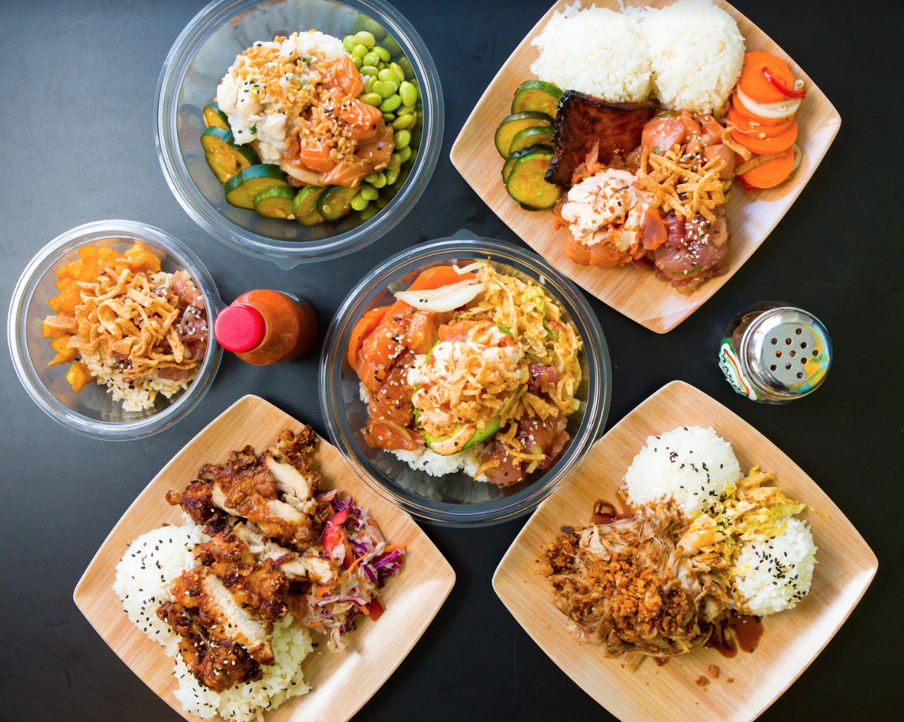 Overhead view of multiple restaurant dishes, including poke, on a dark table