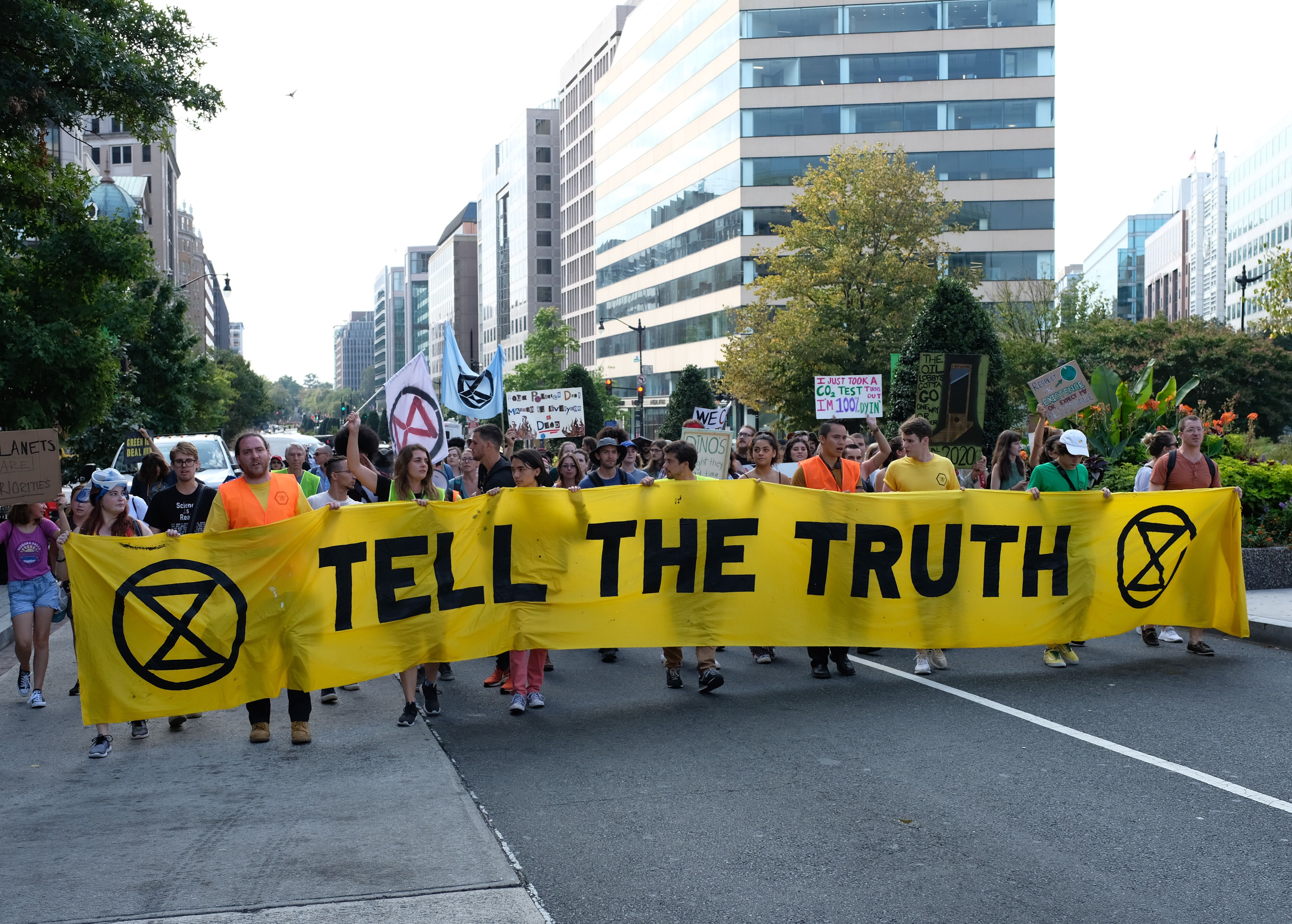 """A group of demonstrators march in the middle of a road carrying a large yellow banner that reads """"Tell The Truth."""""""
