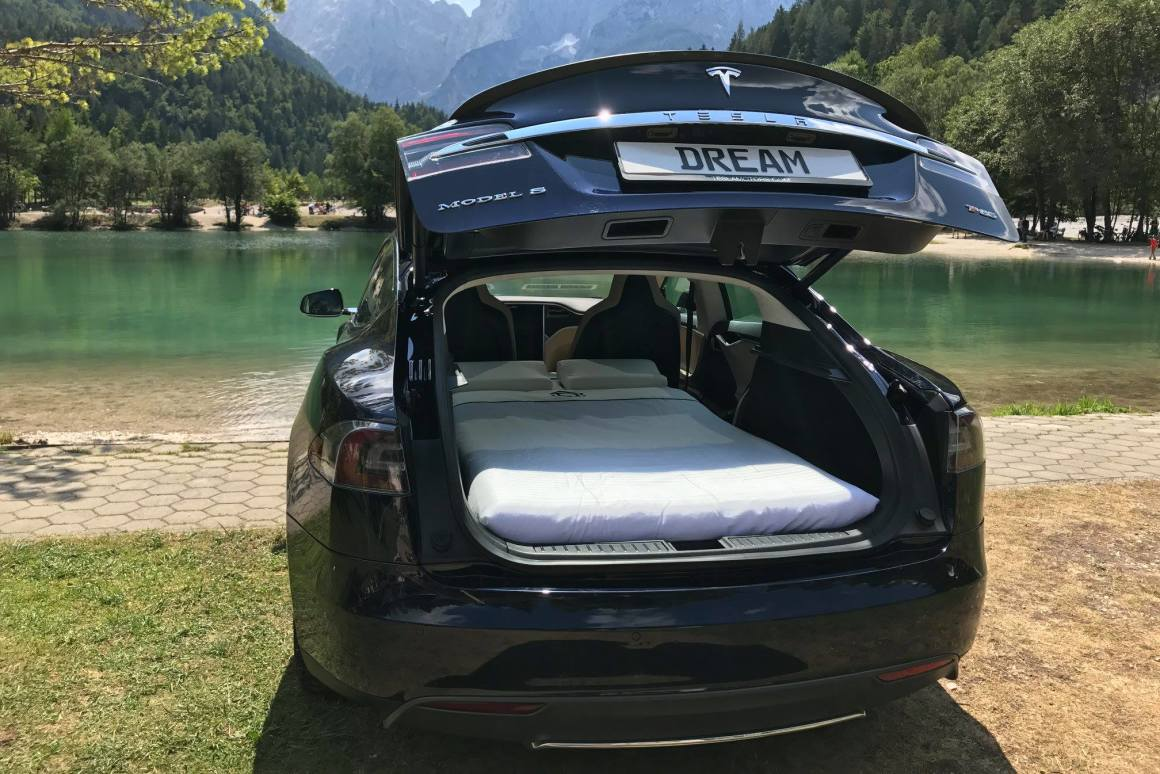 A Tesla car has its back hatch door open and a two-person bed inside. The background is a mountainous lake.