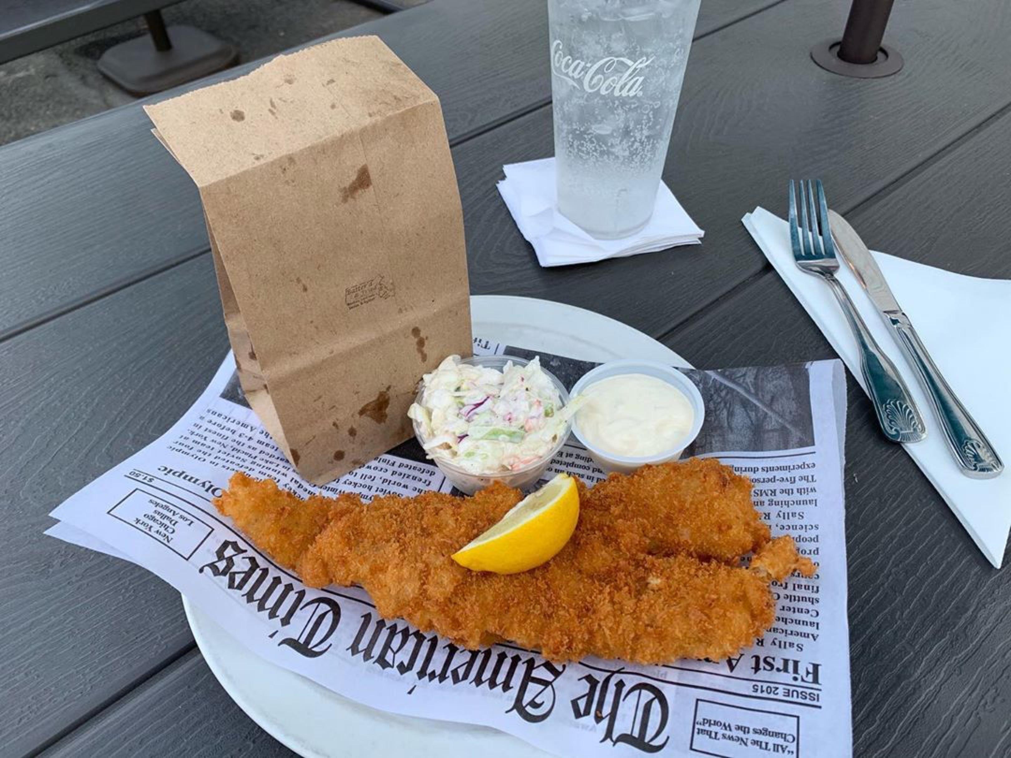 a platter of fried fish, slaw served on newspaper