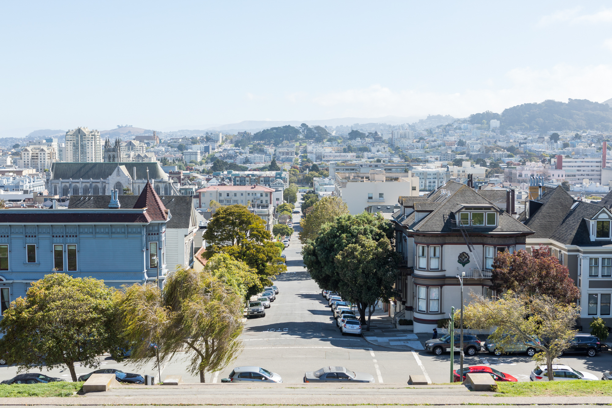 An aerial view of a street and city buildings in San Francisco. The street is lined with trees. In the distance are hills and mountains.