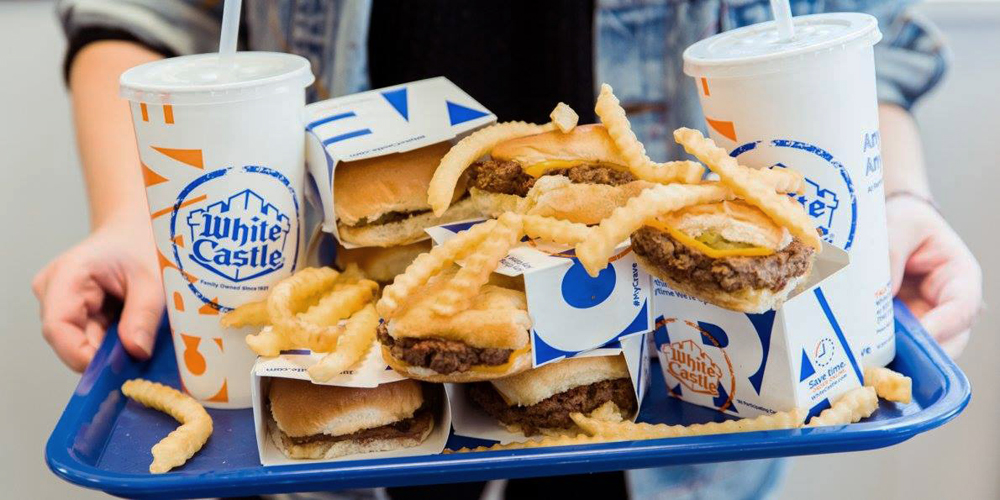 A tray overflowing with White Castle sliders, crinkle cut fries, and sodas.