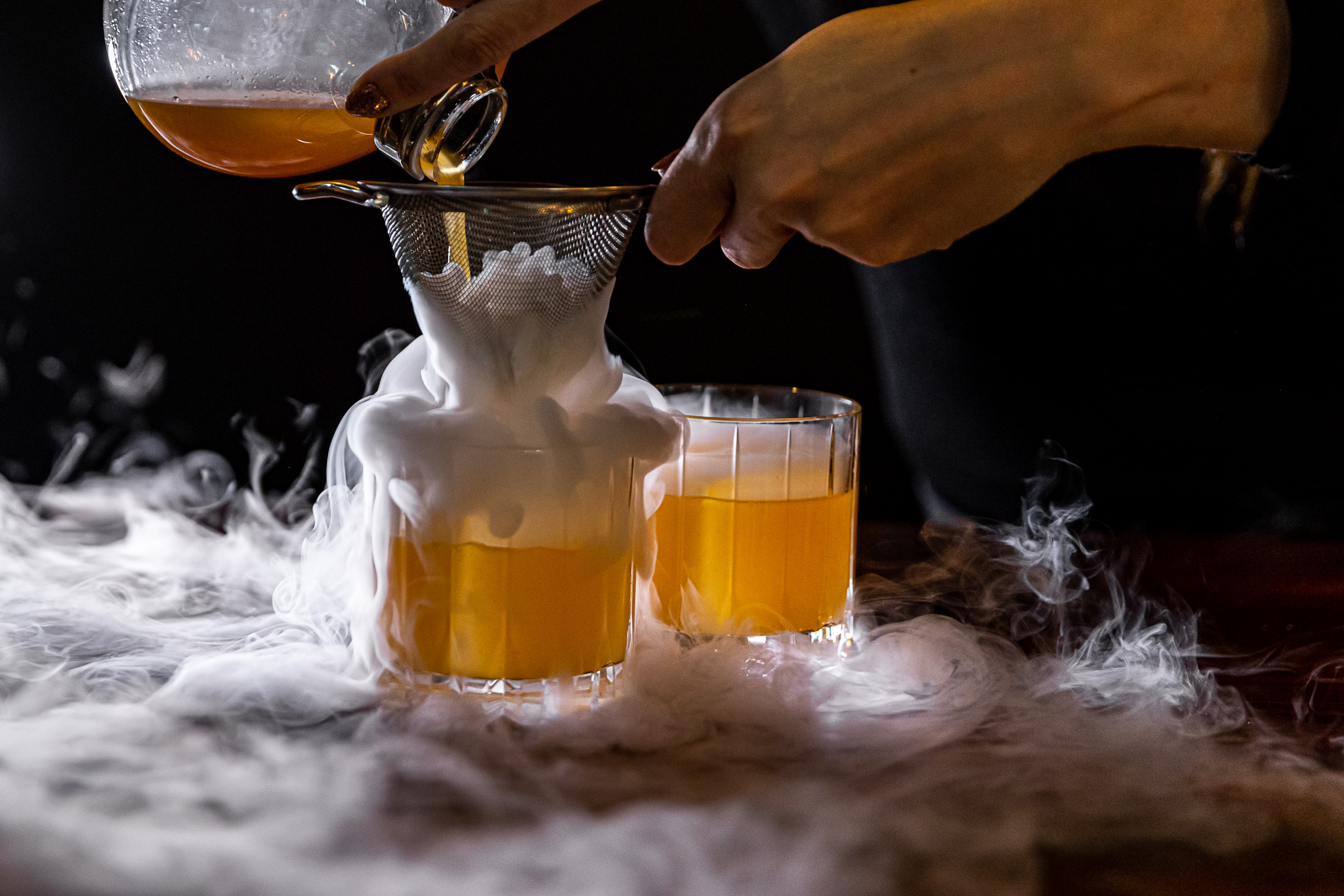 A woman's hand pours yellow liquid from a glass coffee pot through a small strainer and into a tumbler with a large ice cube. Wisps of smoke from dry ice swirl around the glass.