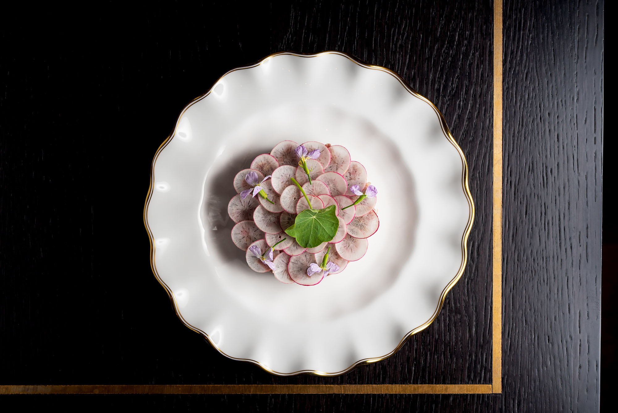 A gorgeous plate of radishes over beef tartare on a simple white plate.