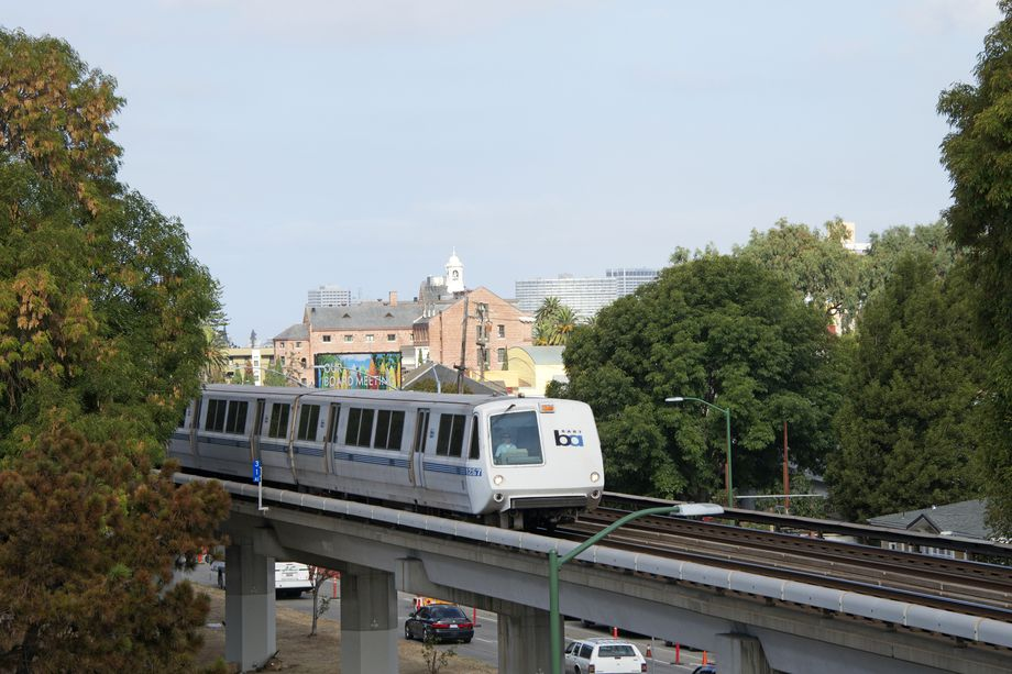 A BART train on an elevated track, passing by some treetops.