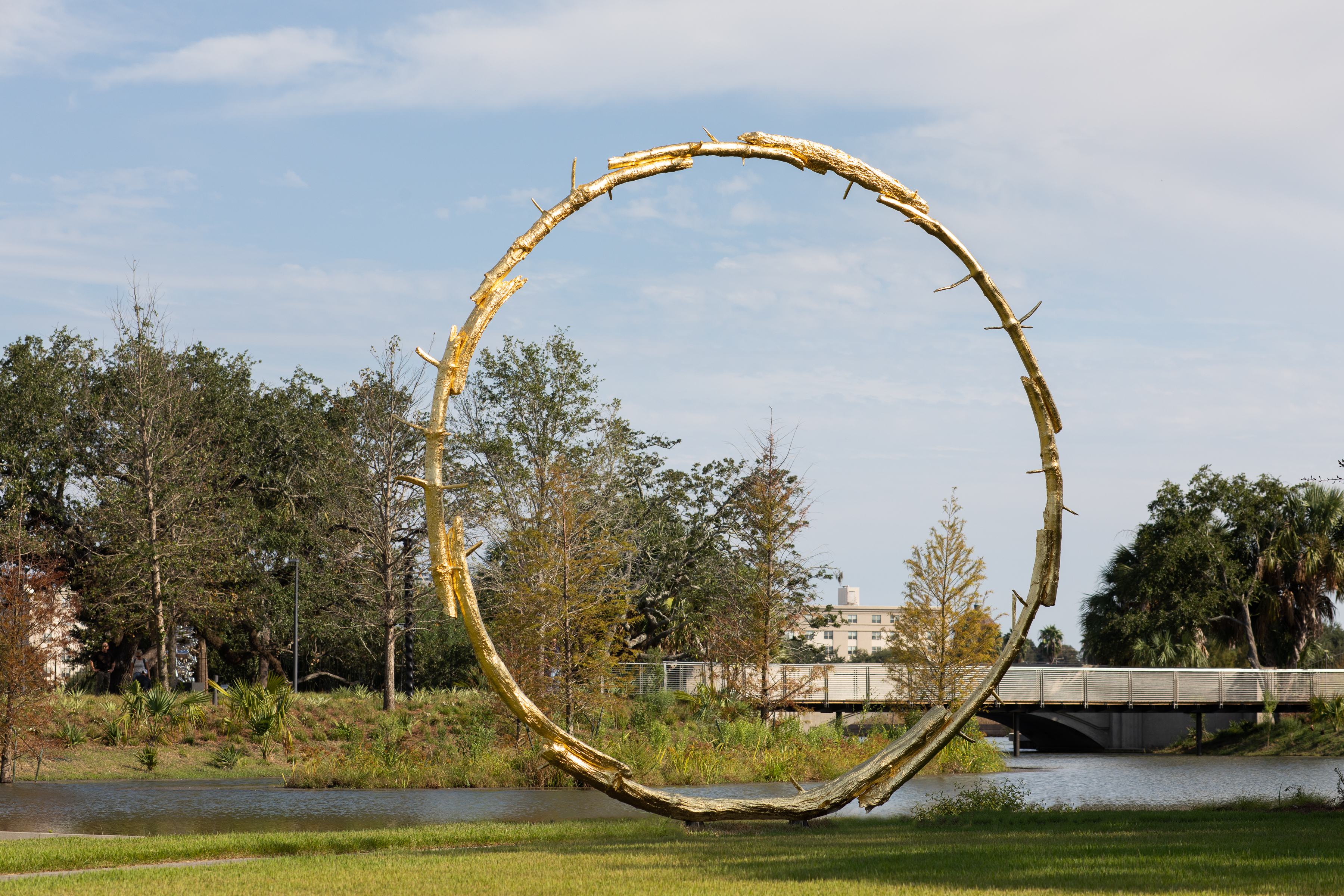 A large gold circular sculpture in a park with trees and lagoons