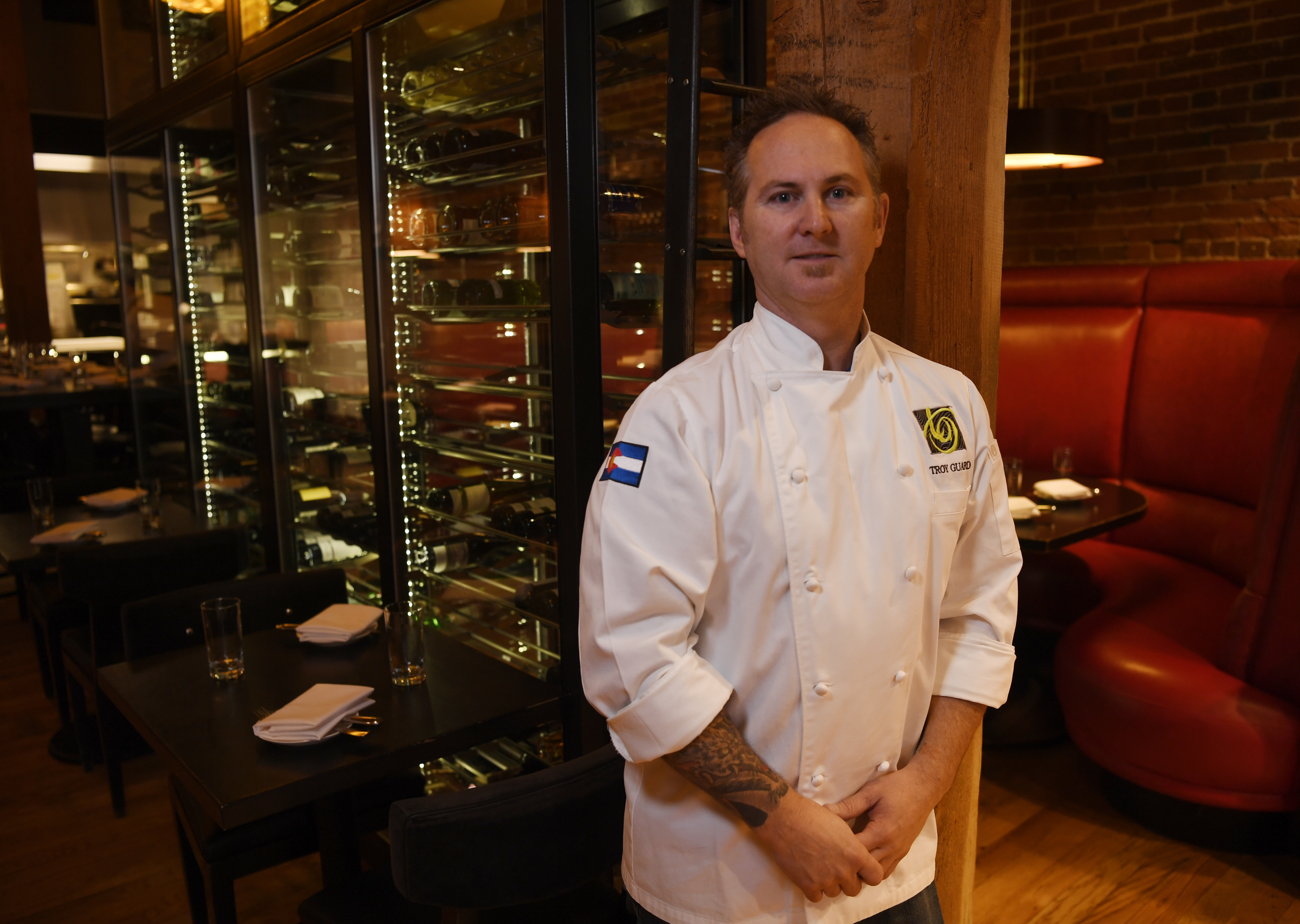 A photo of TAG restaurant group chef and owner Troy Guard standing with his arms together in front of him. Wine bottle racks in his TAG restaurant are visible behind him.