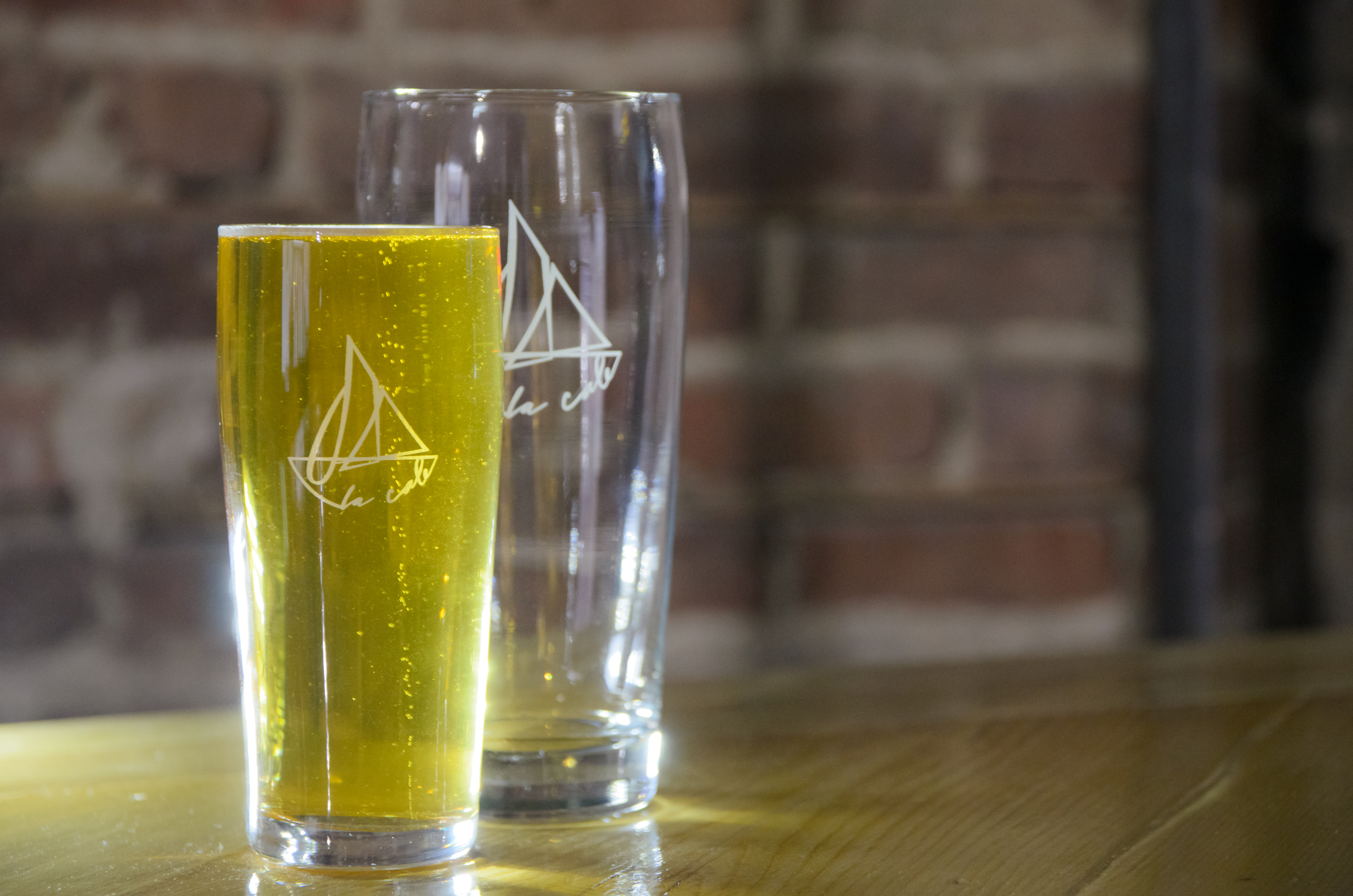 Two glasses with a yacht design on them on a table in front of a brick background.