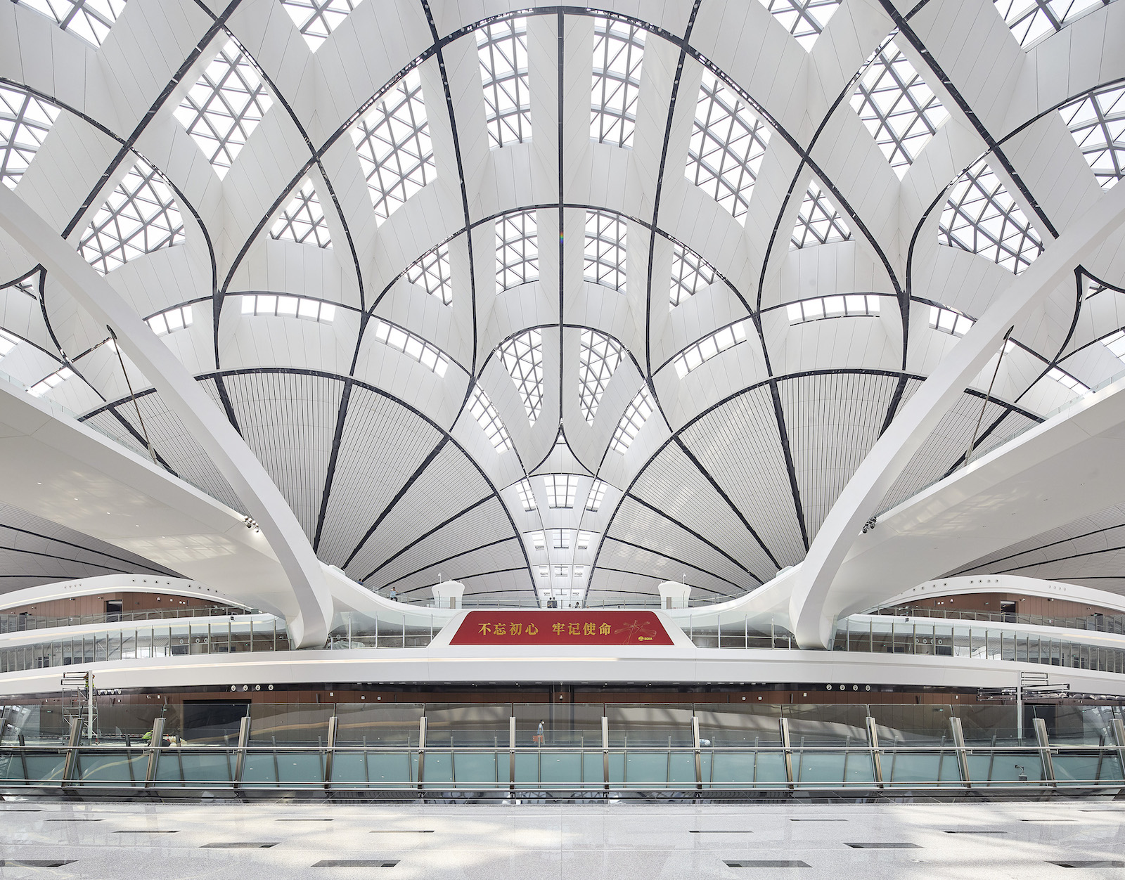 Baggage claim area with elaborate white geometric curving ceiling.