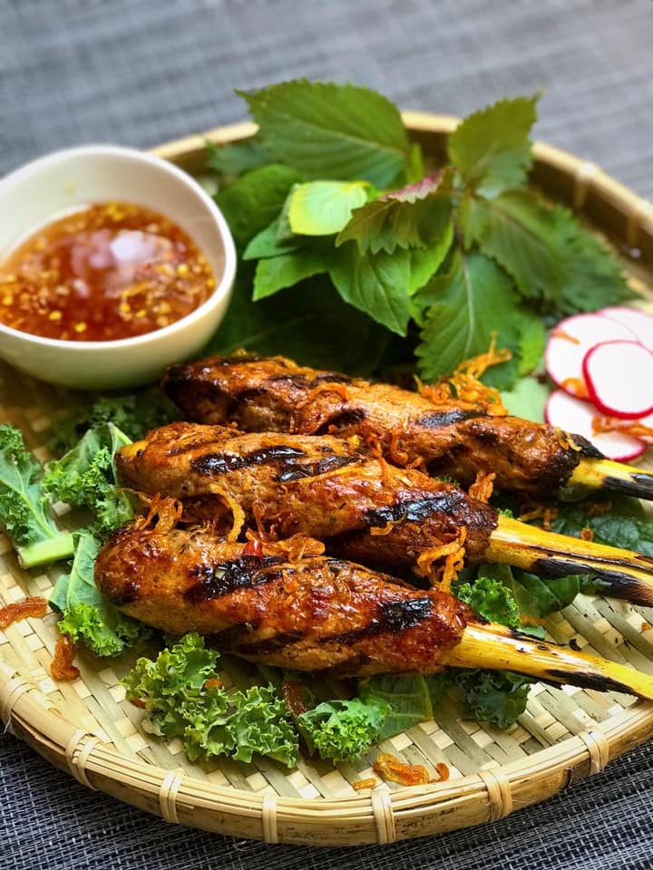 Duck on lemongrass skewers on a bed of greens