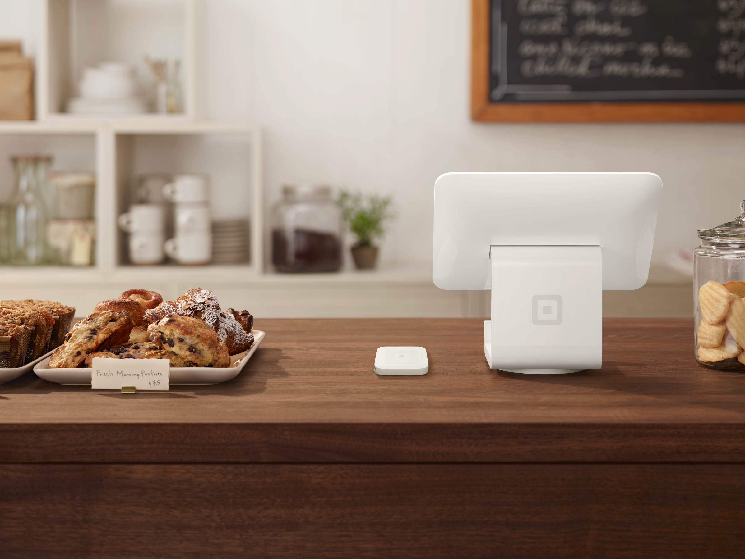 A white Square stand and contactless card reader sits on a cafe counter with pastries.