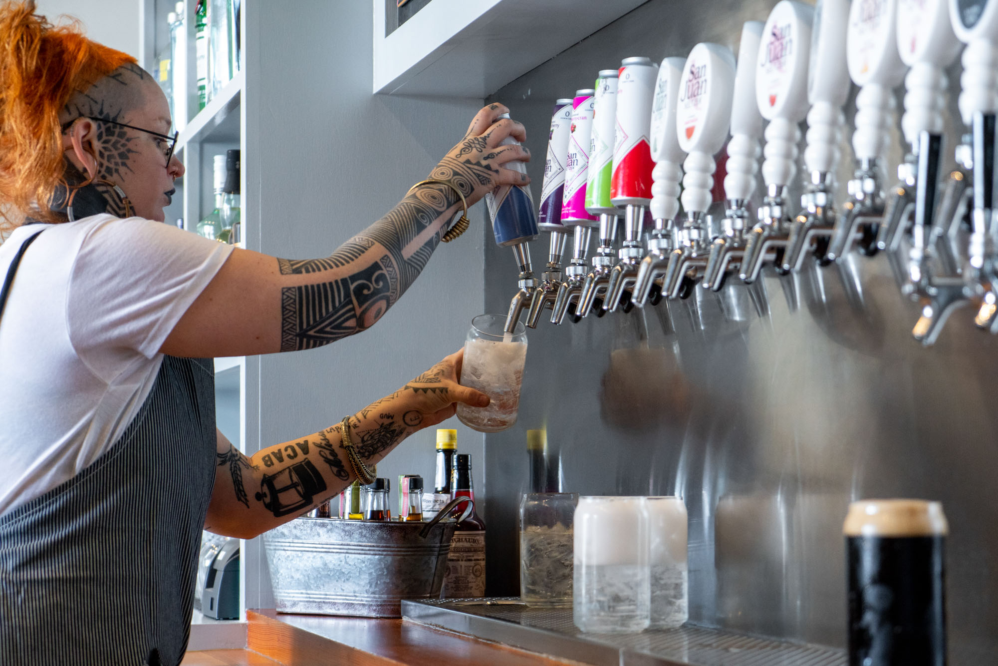 A woman with tattoos pouring cups of hard seltzer from many taps