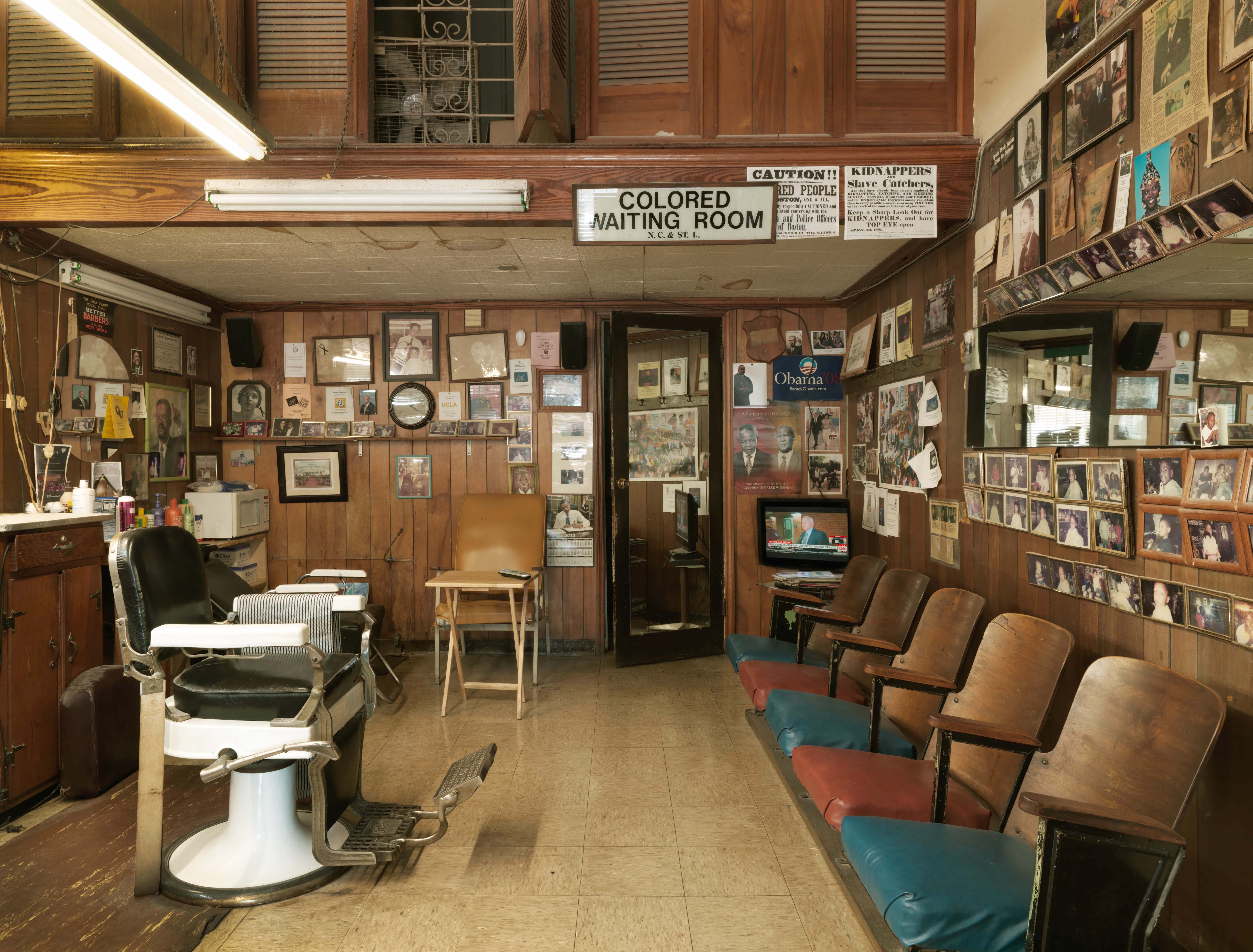 The preserved interior of a '50s area barber shop in Alabama, including a bank of wooden chairs, a barber chair, and a photo collection lining the walls.