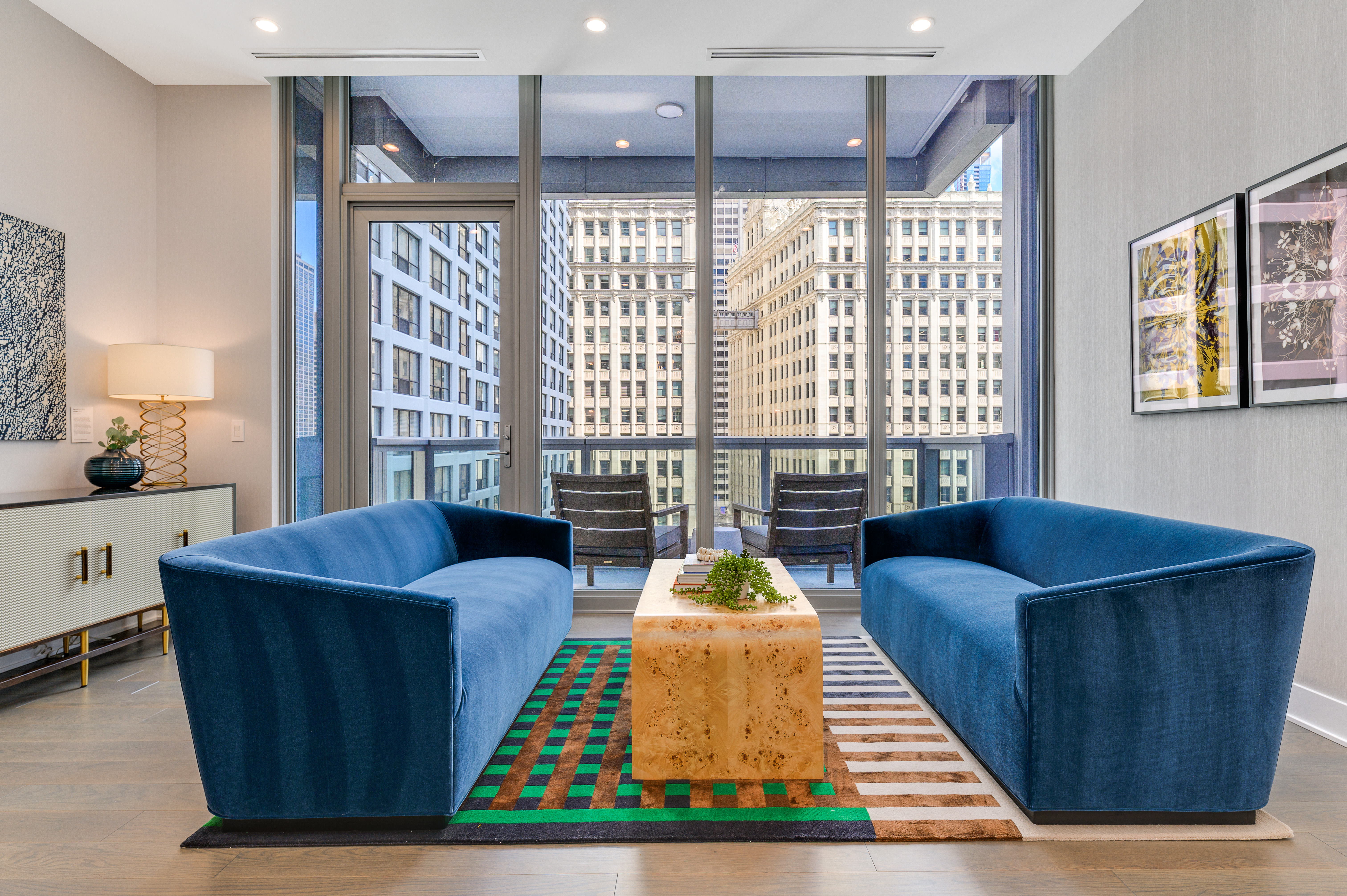 A living room with two blue couches on either side a wooden coffee table. The room connects to a balcony overlooking a cluster of taller buildings.