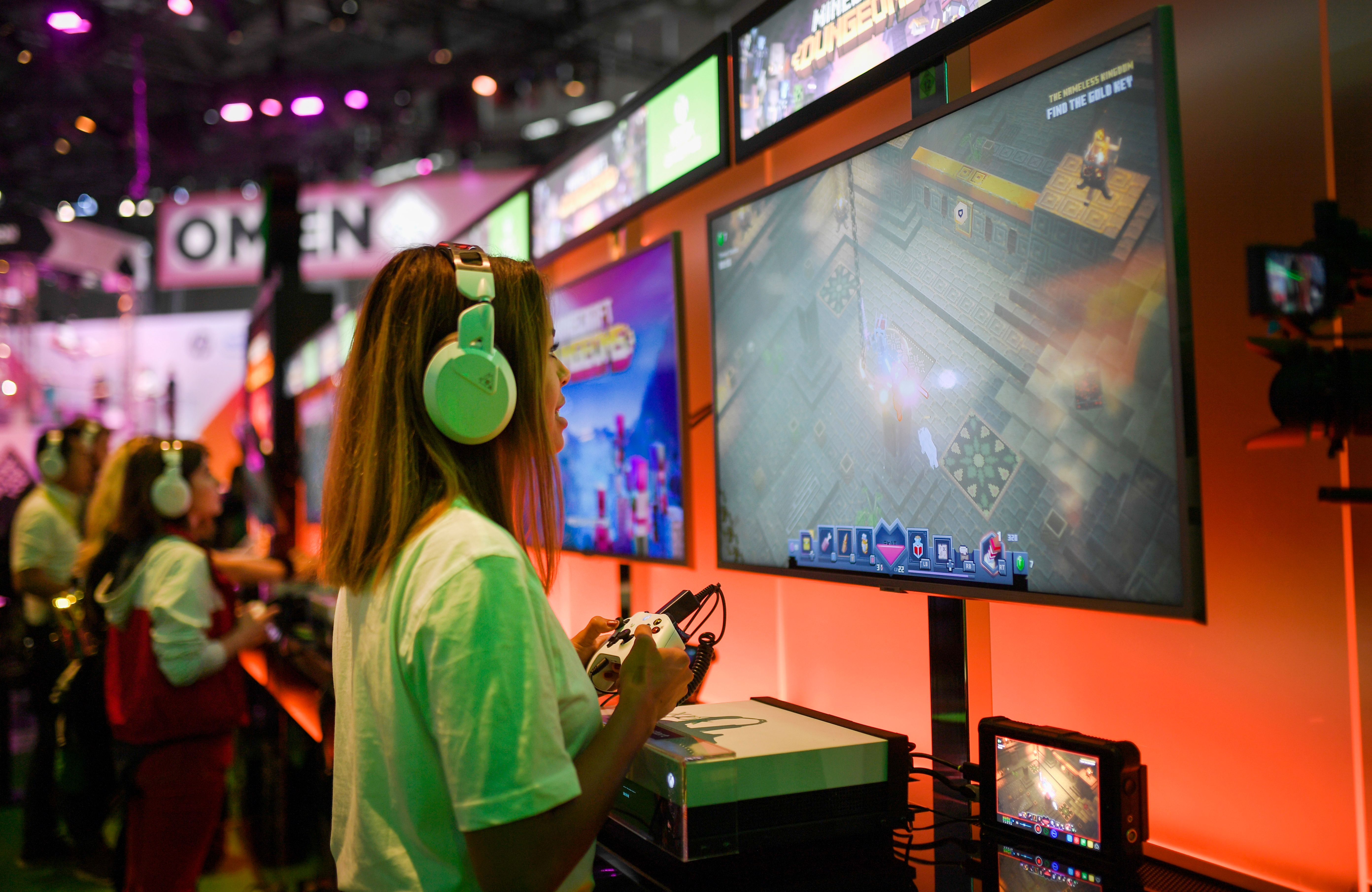 A woman wearing headphones plays at the Xbox stand during the media day of the Gamescom video games trade fair in Cologne, Germany.