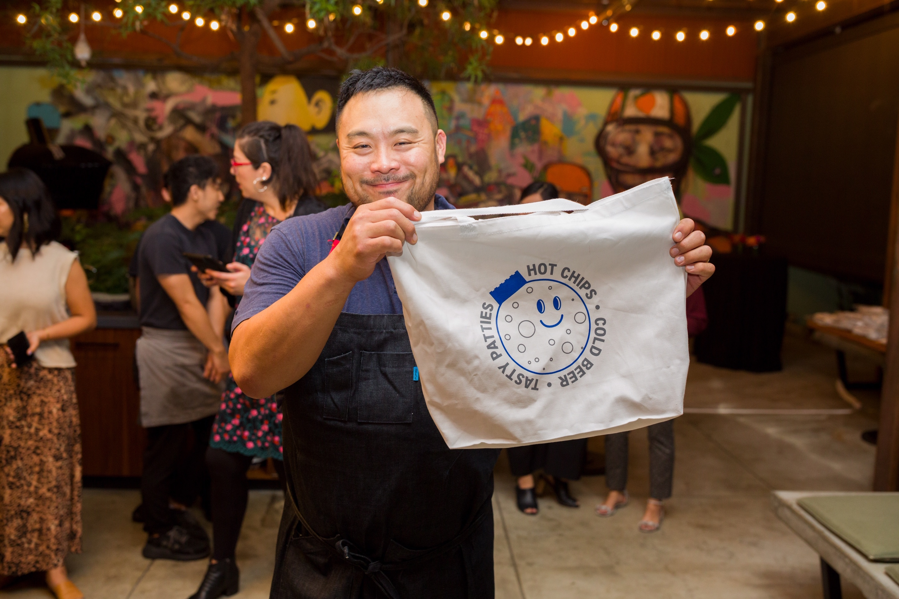 A chef holds up a tote