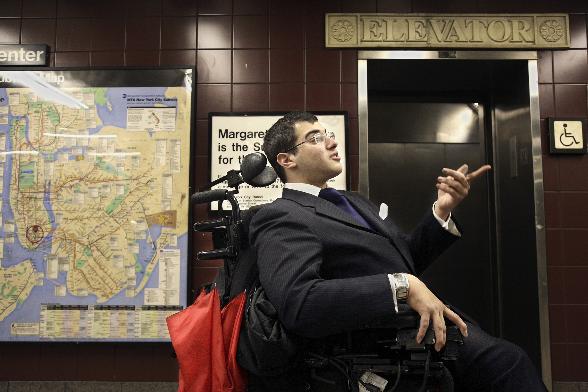 A man wearing a suit in a wheelchair in front of an elevator.