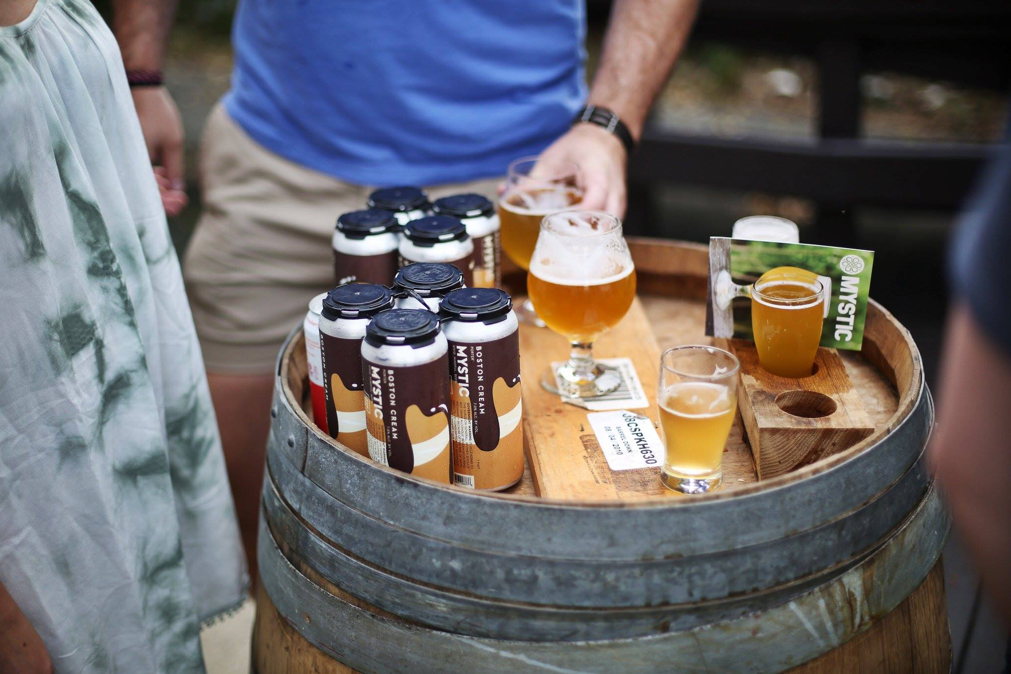 A glass of beer and beer cans stand on top of a barrel; people are standing around the barrel, although only some legs and arms are visible.