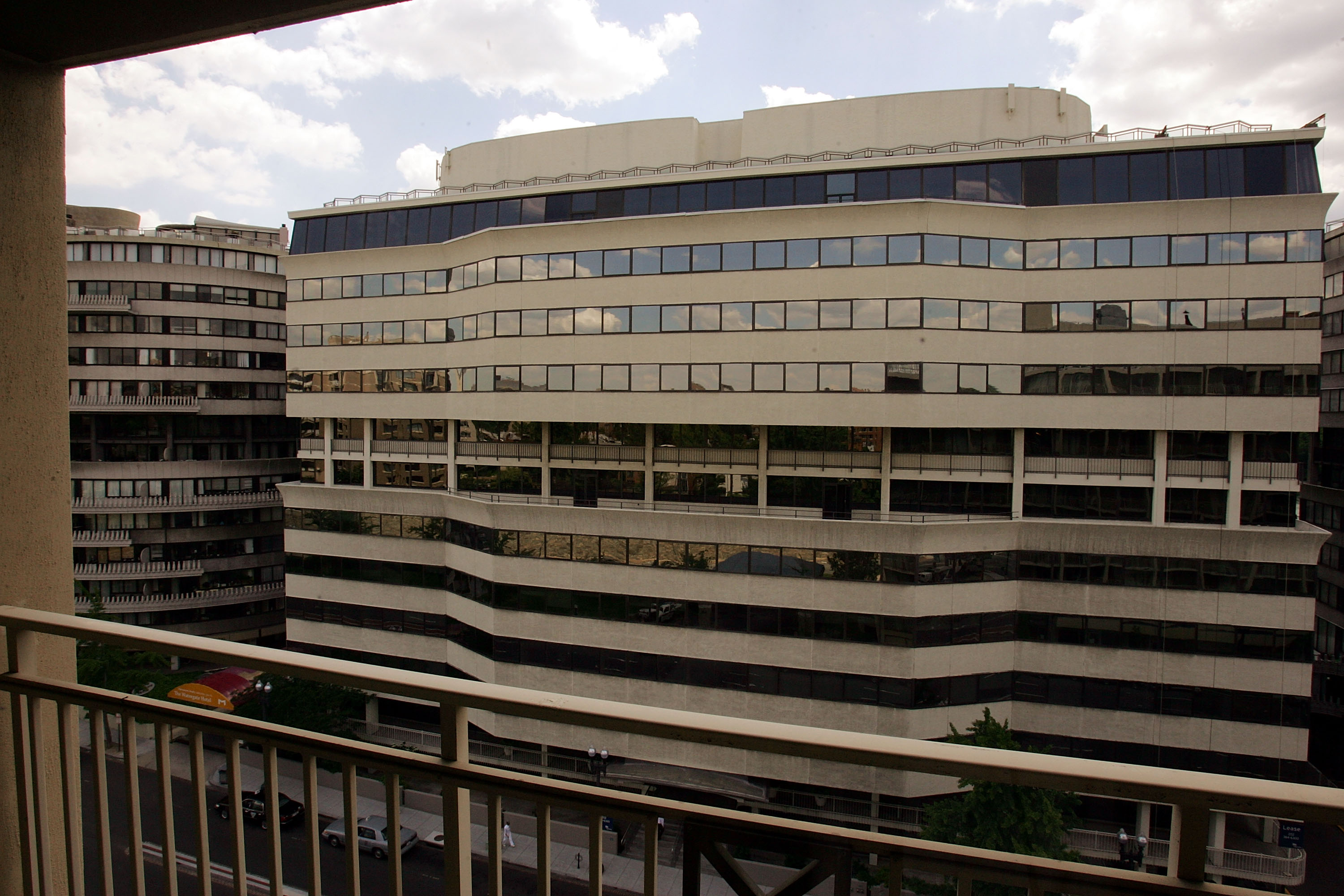 A 1960s office building with horizontal glass panels seen from the balcony of a building across the street.