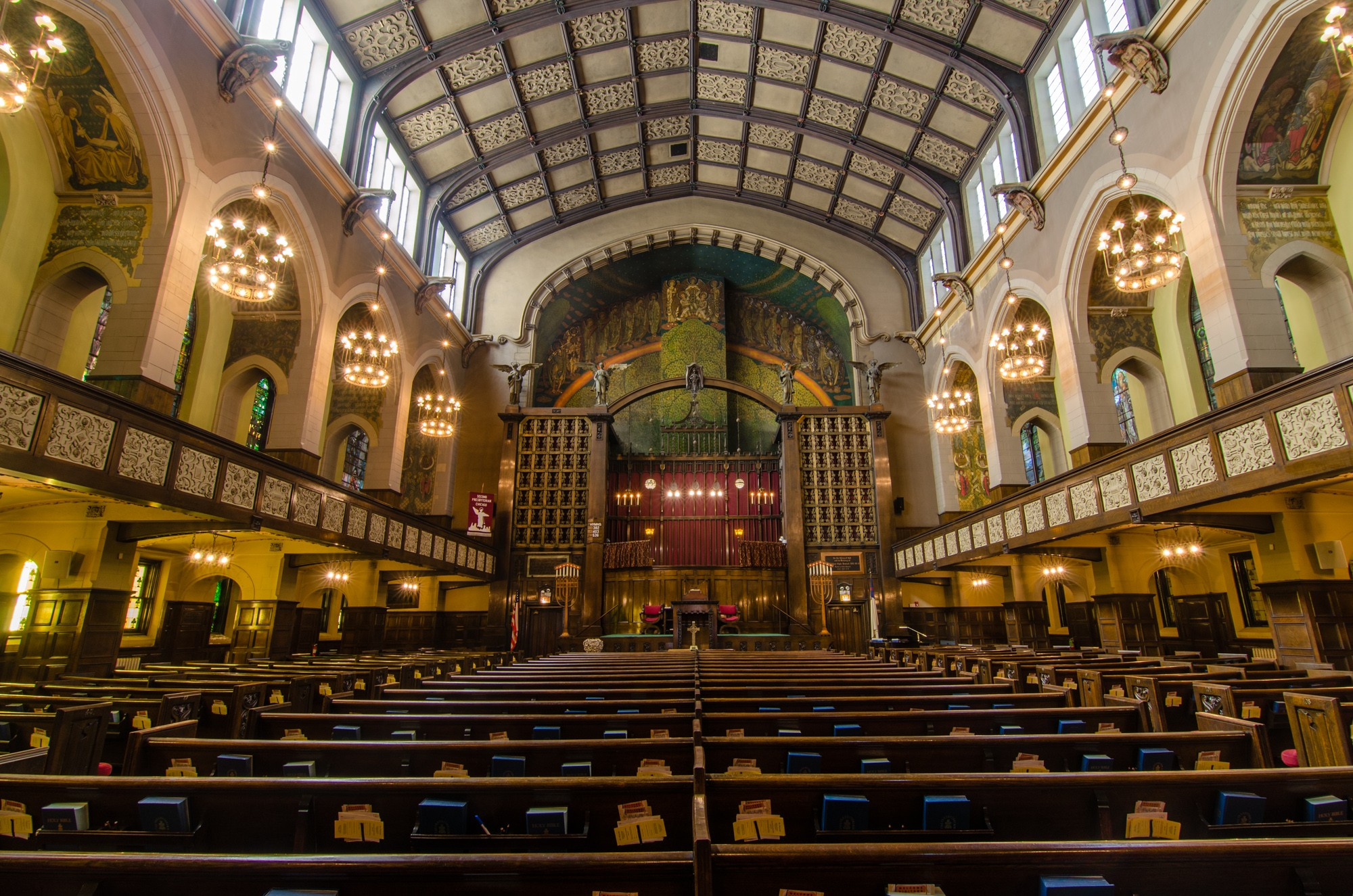 A cavernous church sanctuary with light plaster walls, wood trim, and rows of pews.