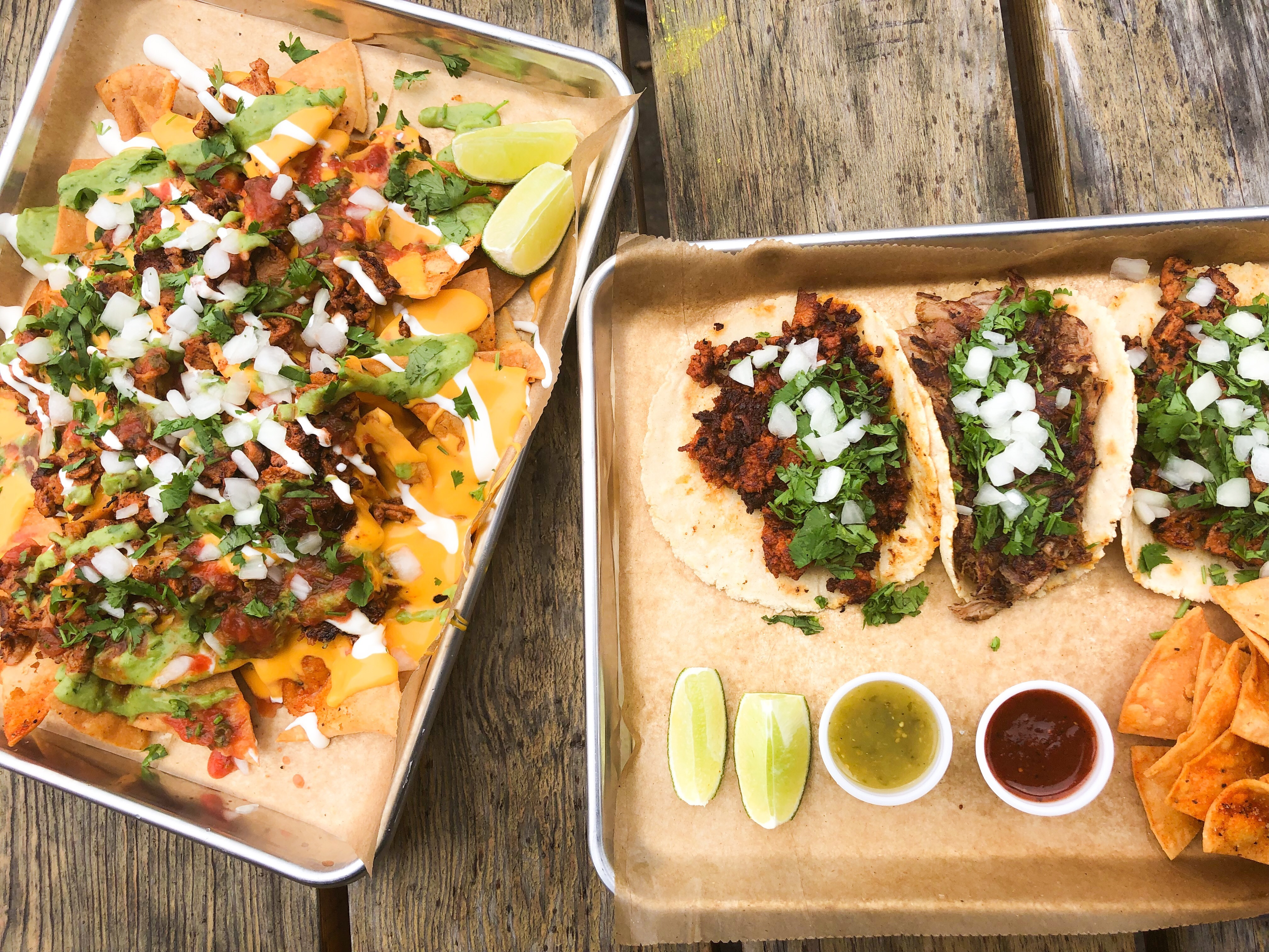 A picture of three tacos — pastor, chorizo, and carnitas — plus pastor nachos at Tight Tacos