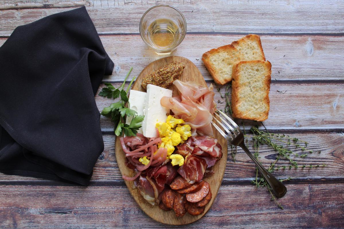 A selection of vegetables, charcuterie, and cheese sits on a wooden board.