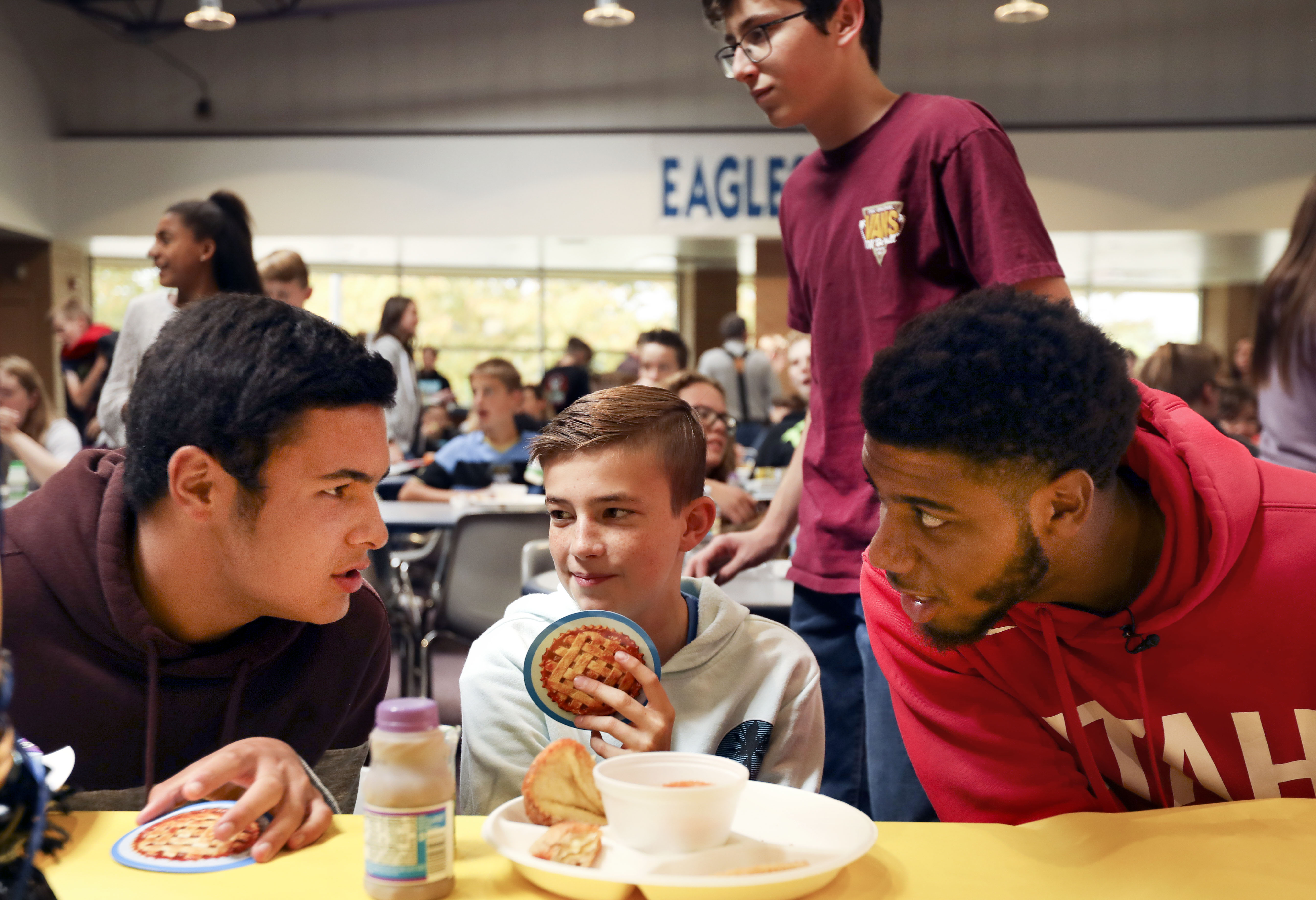 Seventh graders Thomas Fili, left, and Zach Schlies eat lunch with Utah Jazz guard Justin Wright-Foreman at Bountiful Junior High School in Bountiful on Friday, Sept. 27, 2019. Wright-Foreman and Jazz forward Stanton Kidd visited the school during Hello Week, a program that teaches students to make a difference with their peers in a simple, fun and impactful way.