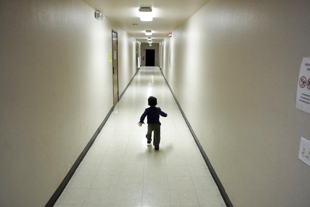 Child runs down hallway in shelter in San Diego