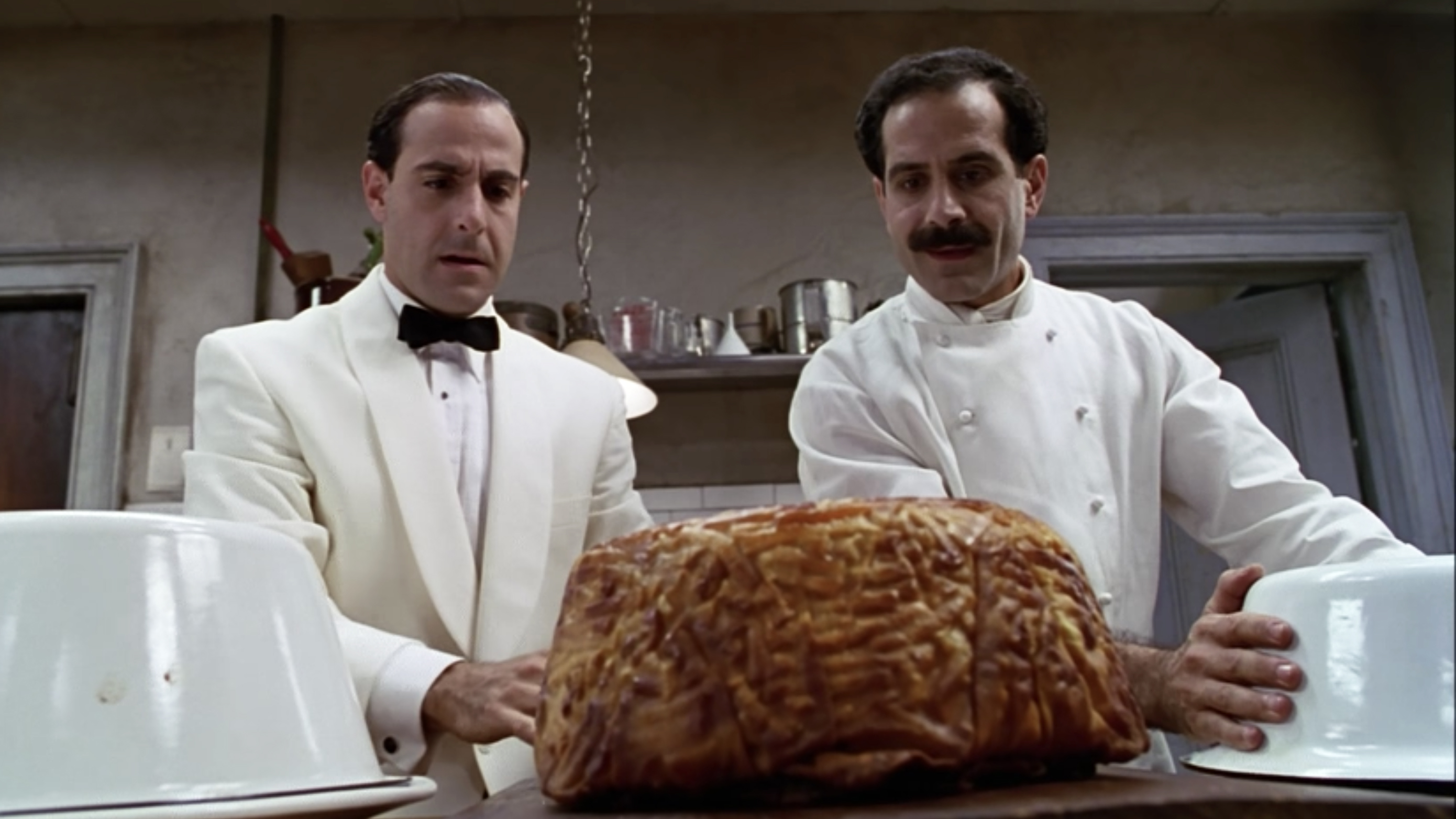 Stanley Tucci and Tony Shalhoub take the Tiimpano, a giant pasta cake, out of its mold.