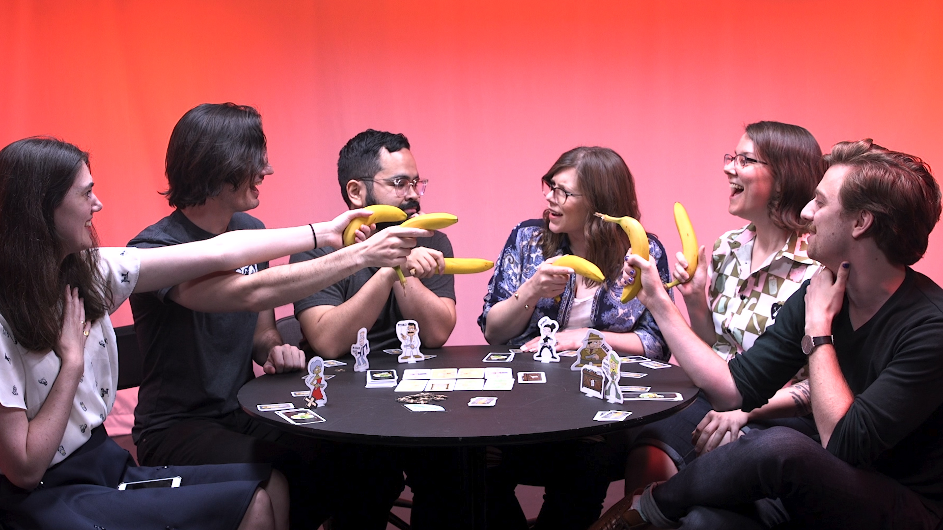 A group of board game players sitting at a table aim bananas at each other.