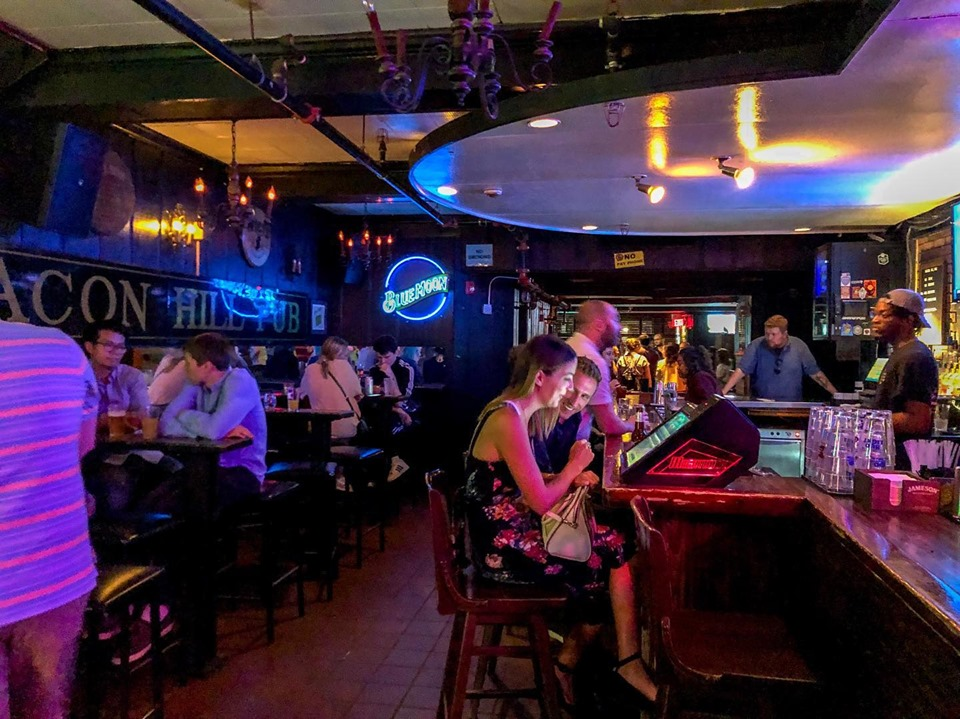 The interior of a dive bar, with a neon Blue Moon sign, happy patrons drinking beer, and more