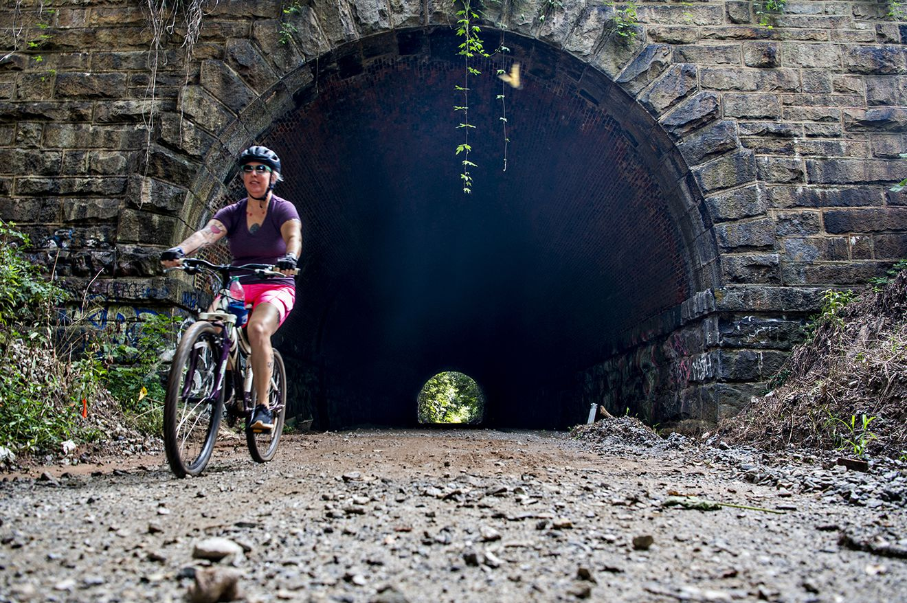 A woman at left rides a bike on a gravel trail through a lone stone tunnel.