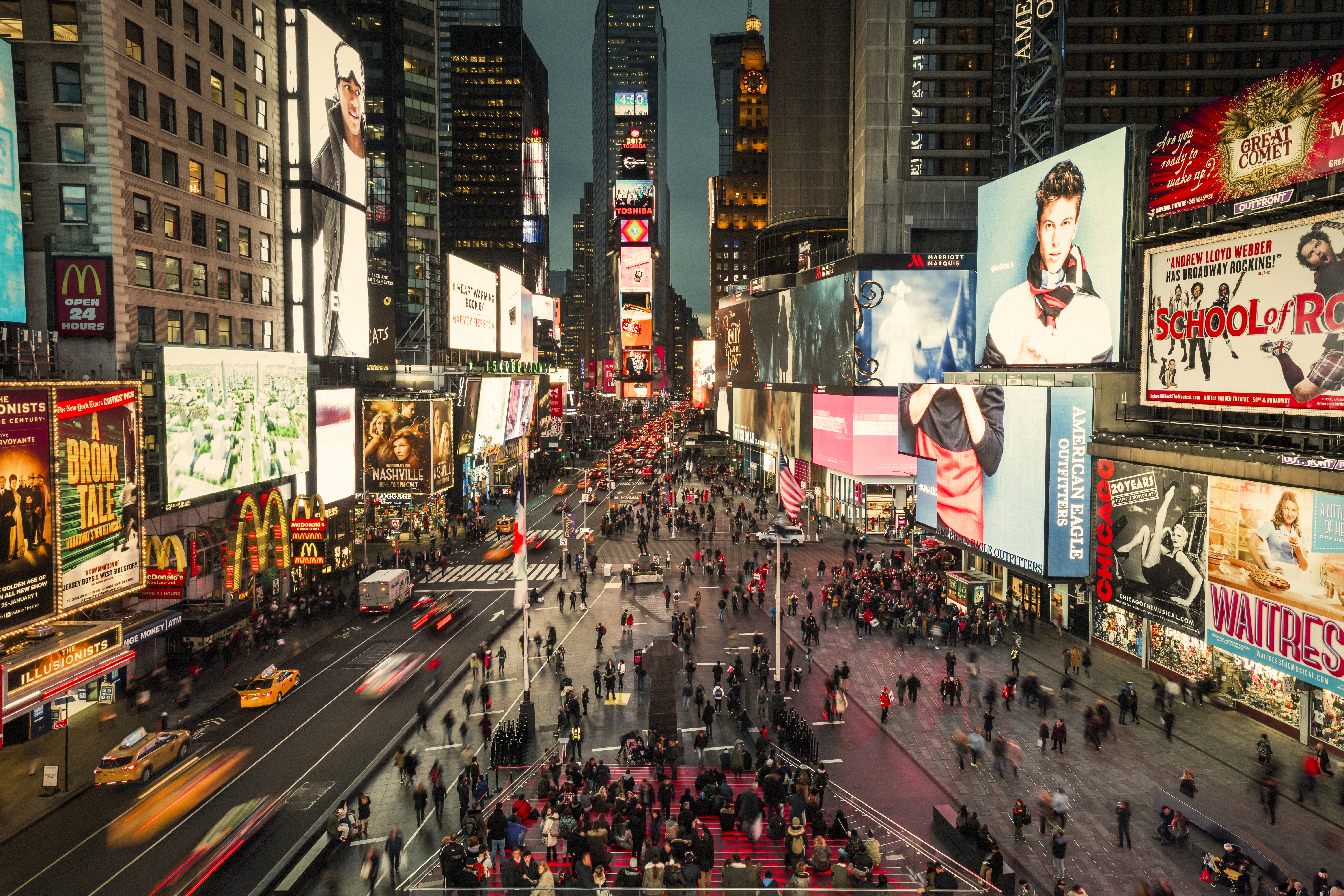 An aerial view of the Time Square pedestrian mall surrounded by many illuminated billboards and signs on buildings. There are people walking in the mall area.
