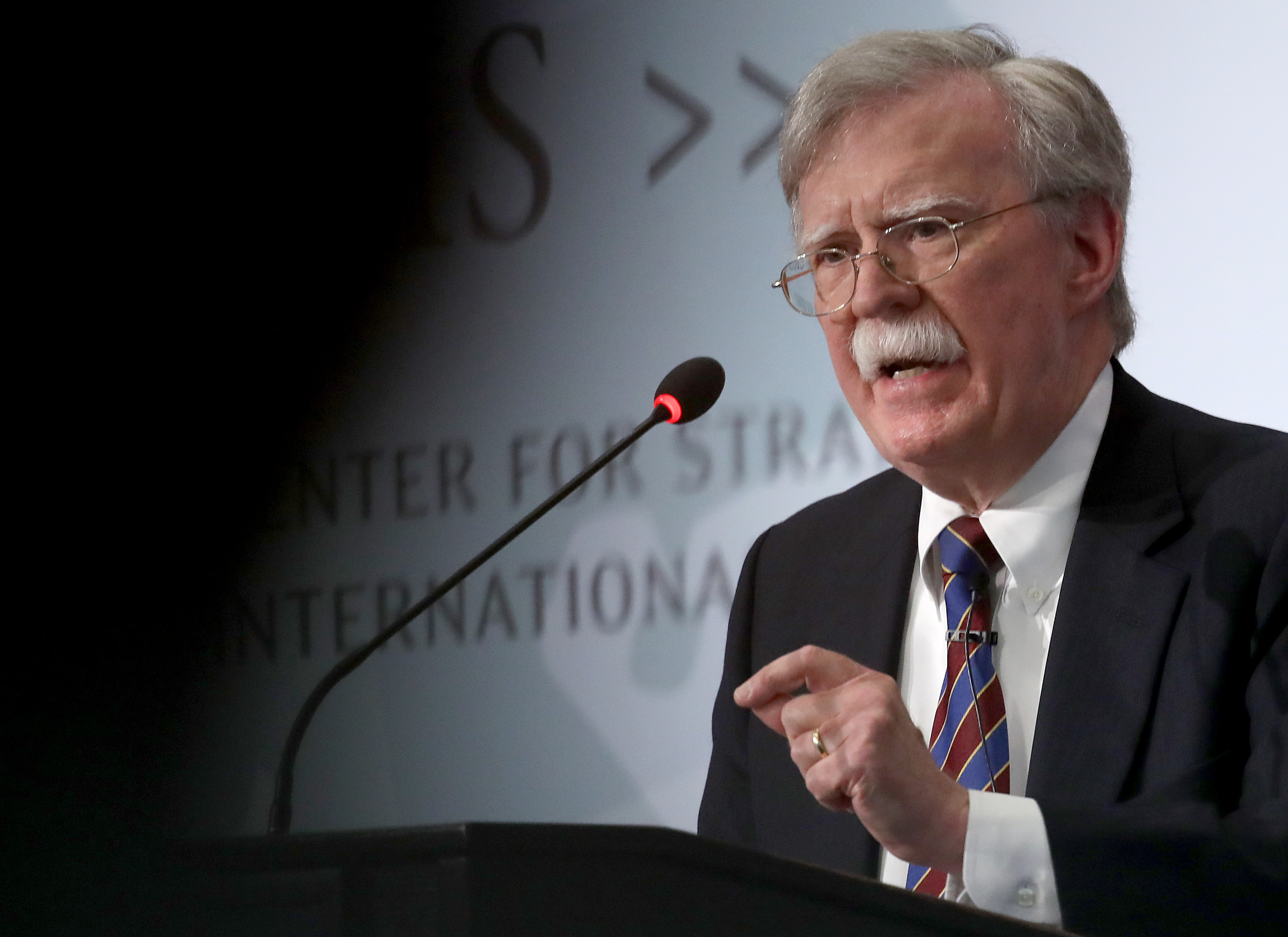 John Bolton speaking at a podium onstage.