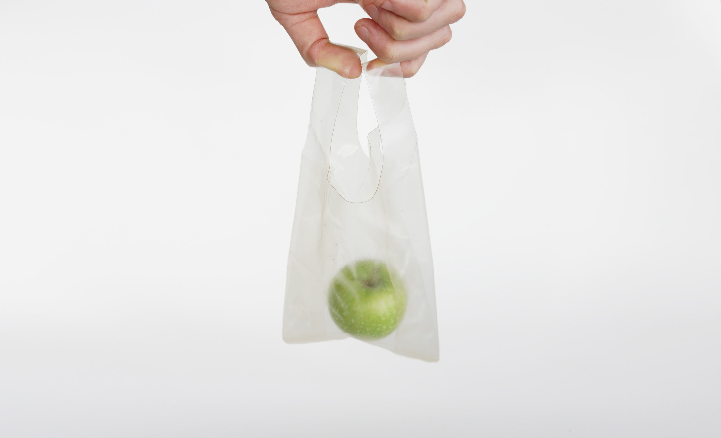 A hand holds a plastic bag containing a green apple.