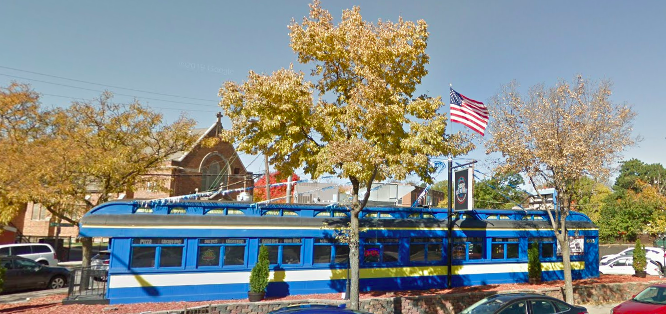 The exterior of the restaurant that looks like an old dining rail car, painted bright blue with cream accents